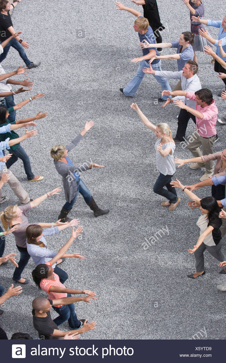 People extending arms to each other in crowd - Stock Image