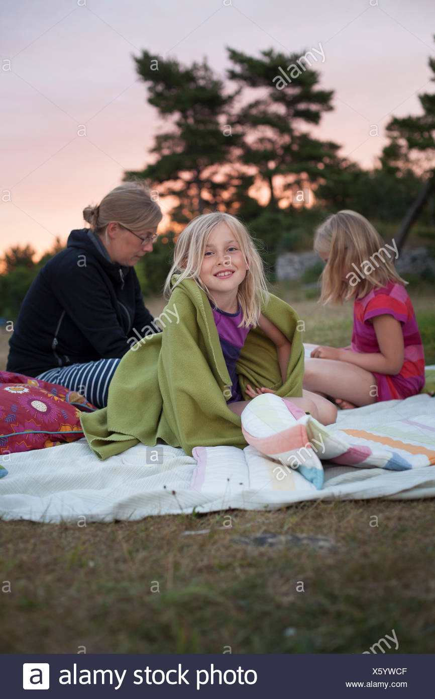 Sweden, Gotland, Faro, Girl (10-11) sitting on picnic blanket with mother and sister (8-9) - Stock Image