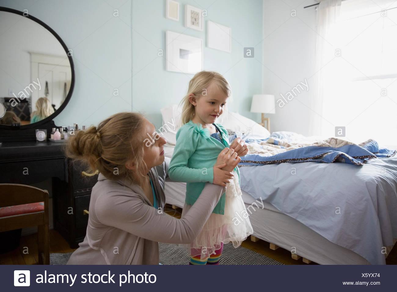 Mother dressing daughter in bedroom - Stock Image