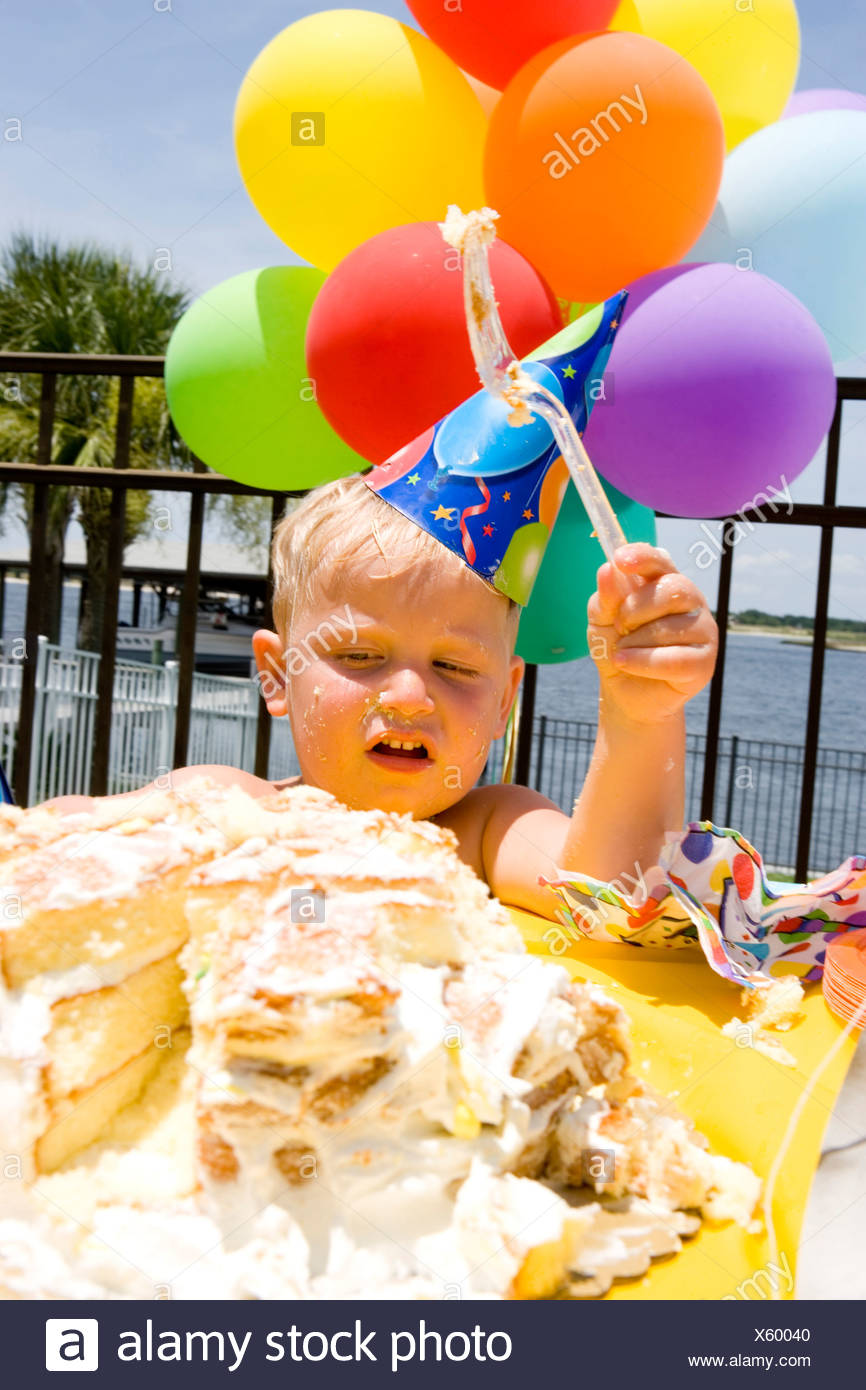 Boy Holding Balloons In Front Of A Birthday Cake