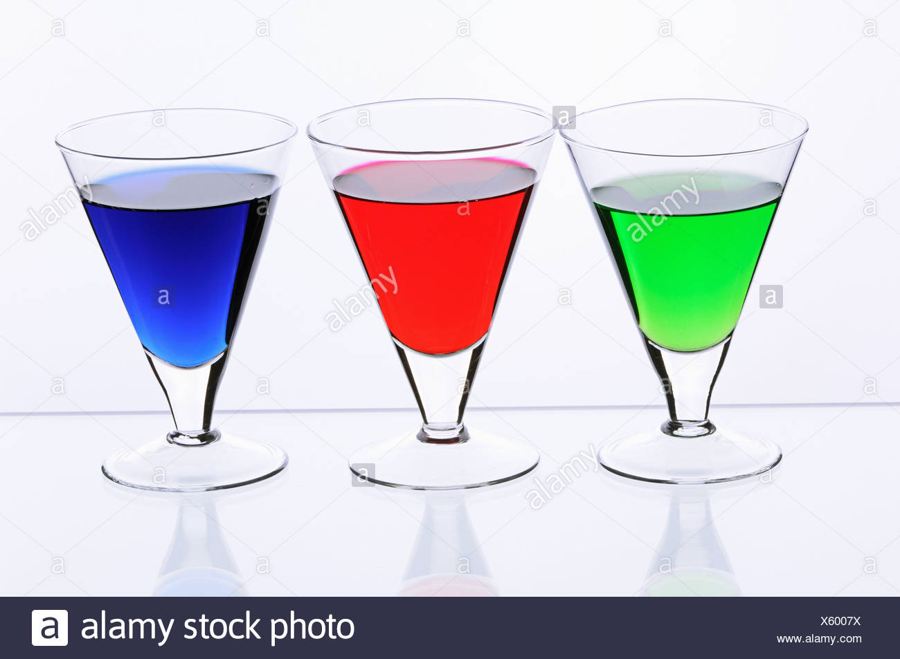 Three transparent glasses with multi-coloured drinks - Stock Image