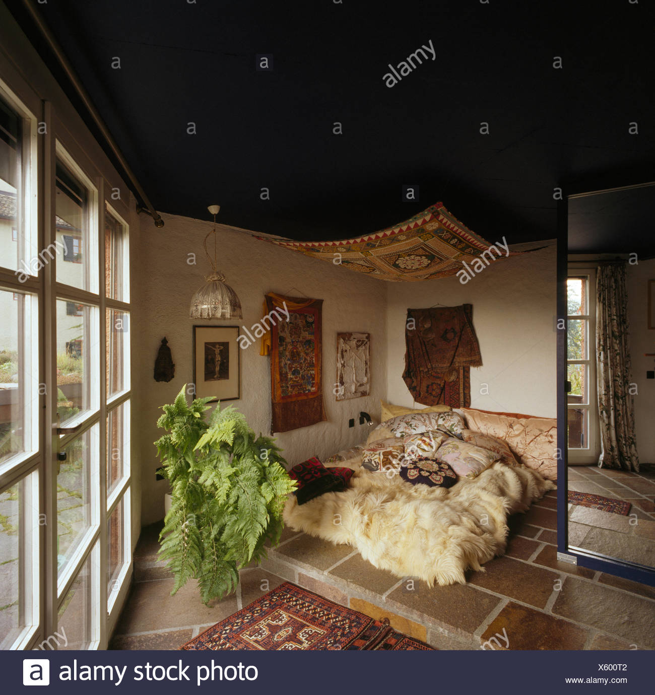 Awning above bed with sheepskin throw in eighties Swedish bedroom - Stock Image
