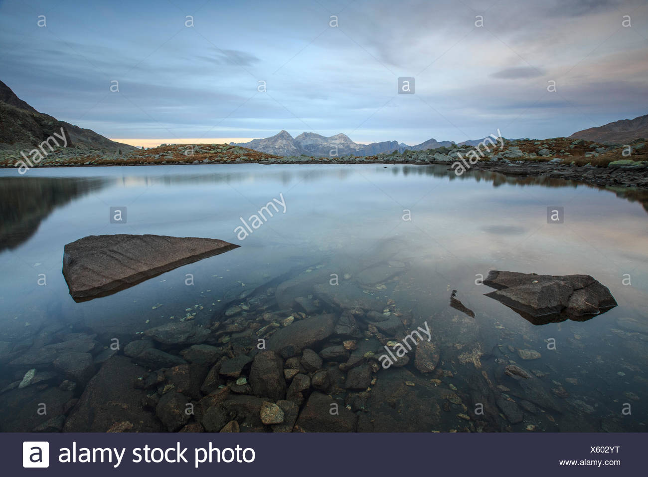 Peaks are reflected in Lake Bergsee at dusk Chiavenna Valley Spluga Valley Switzerland Europe - Stock Image