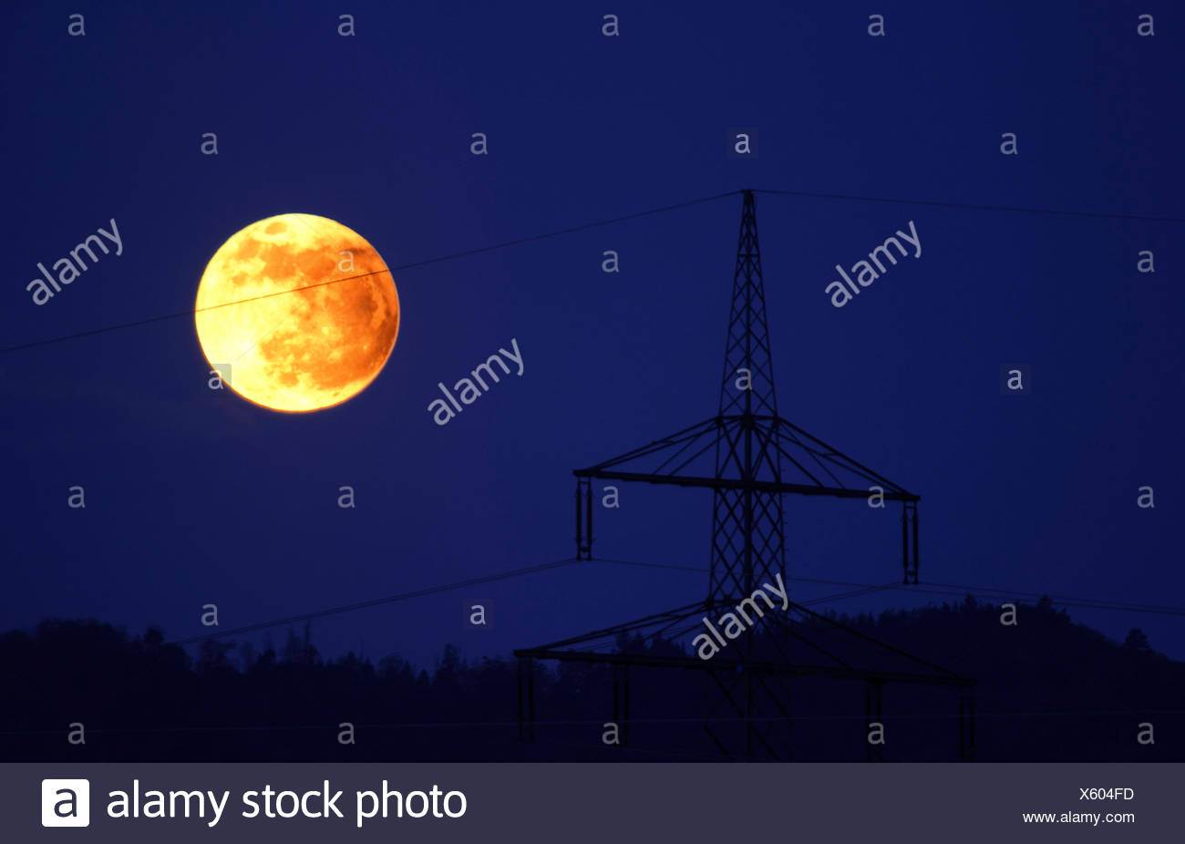night shot with full moon and electricity pylon, Germany - Stock Image