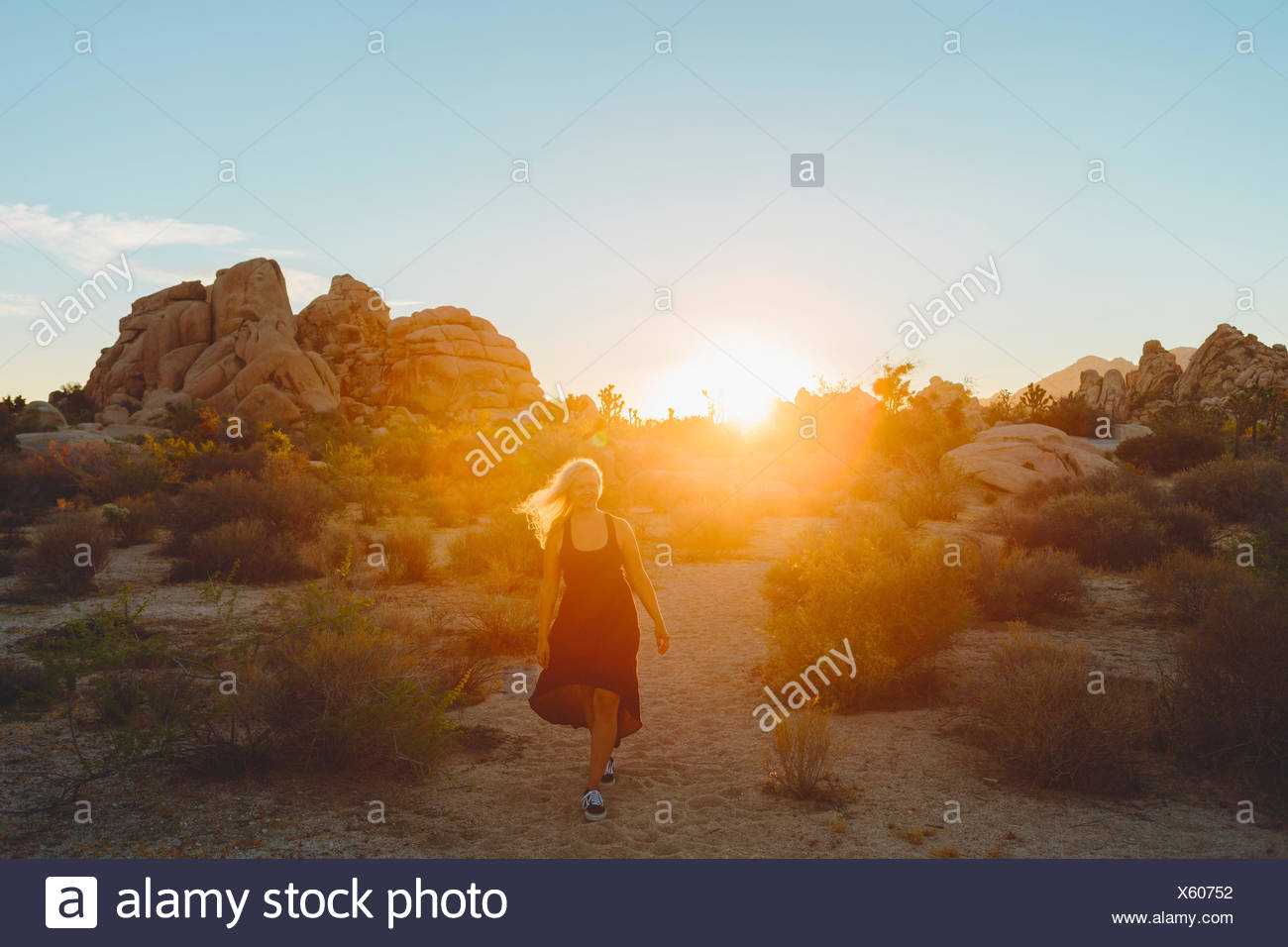 USA, California, Joshua Tree National Park, Woman wearing dress hiking at sunset - Stock Image