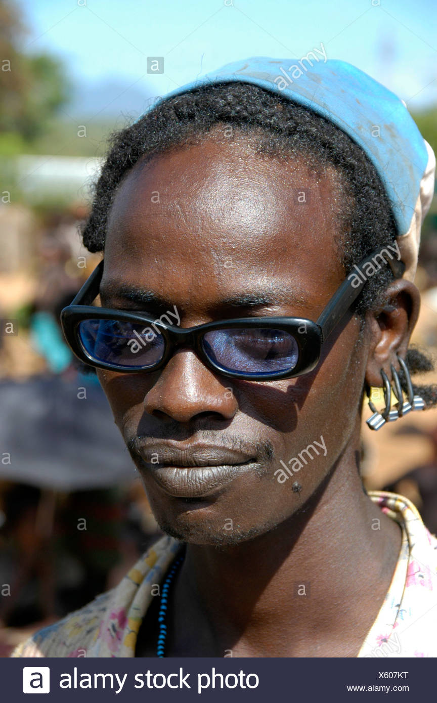 Man wearing black horn-rimmed glasses, portrait, at the markets in Dimeka, Ethiopia, Africa - Stock Image