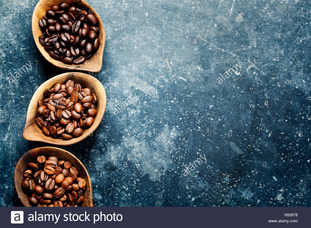 Top view of three different varieties of coffee beans on dark vintage background - Stock Image
