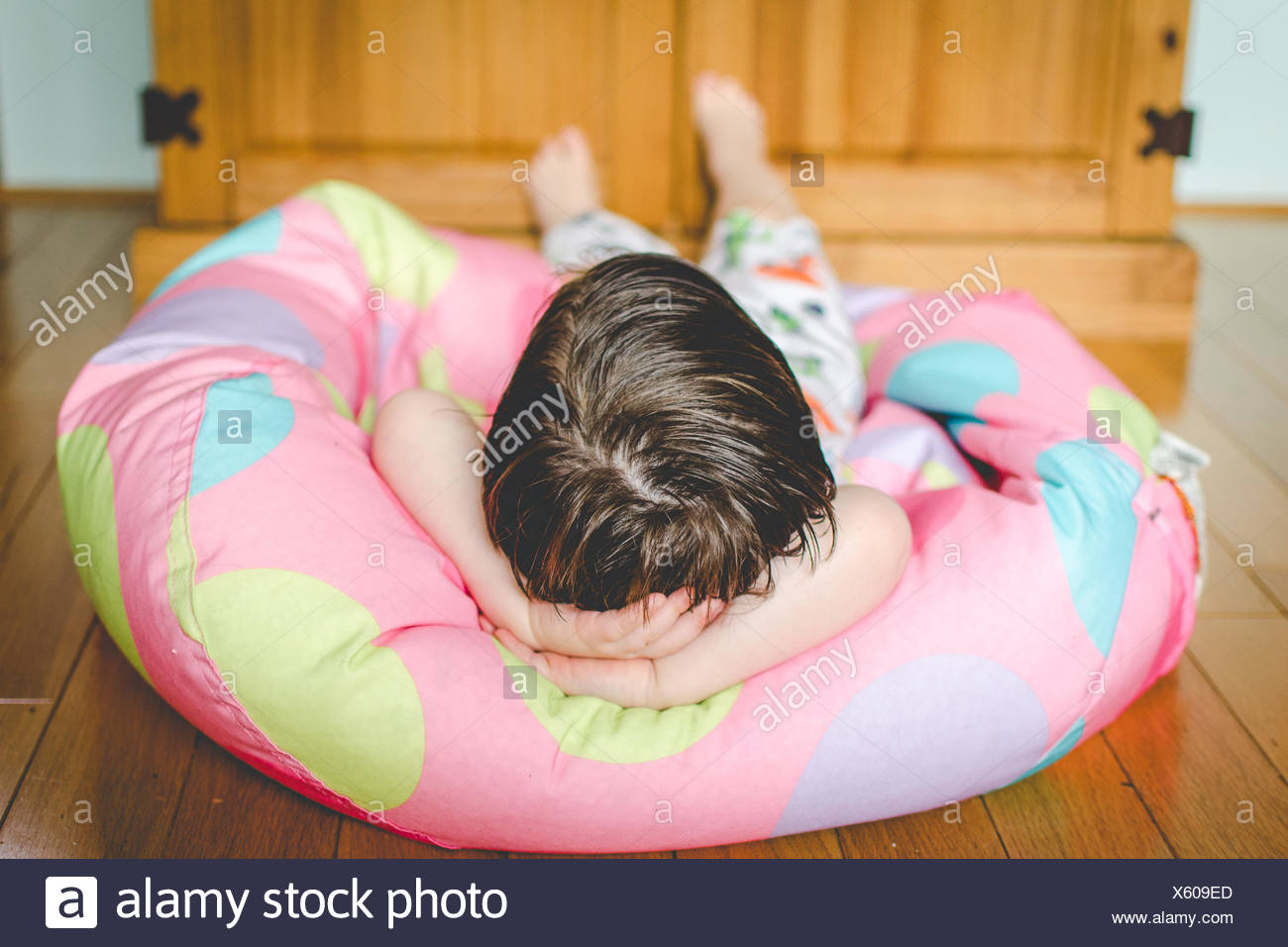 Little boy lying on bean bag chair with hands behind his head - Stock Image