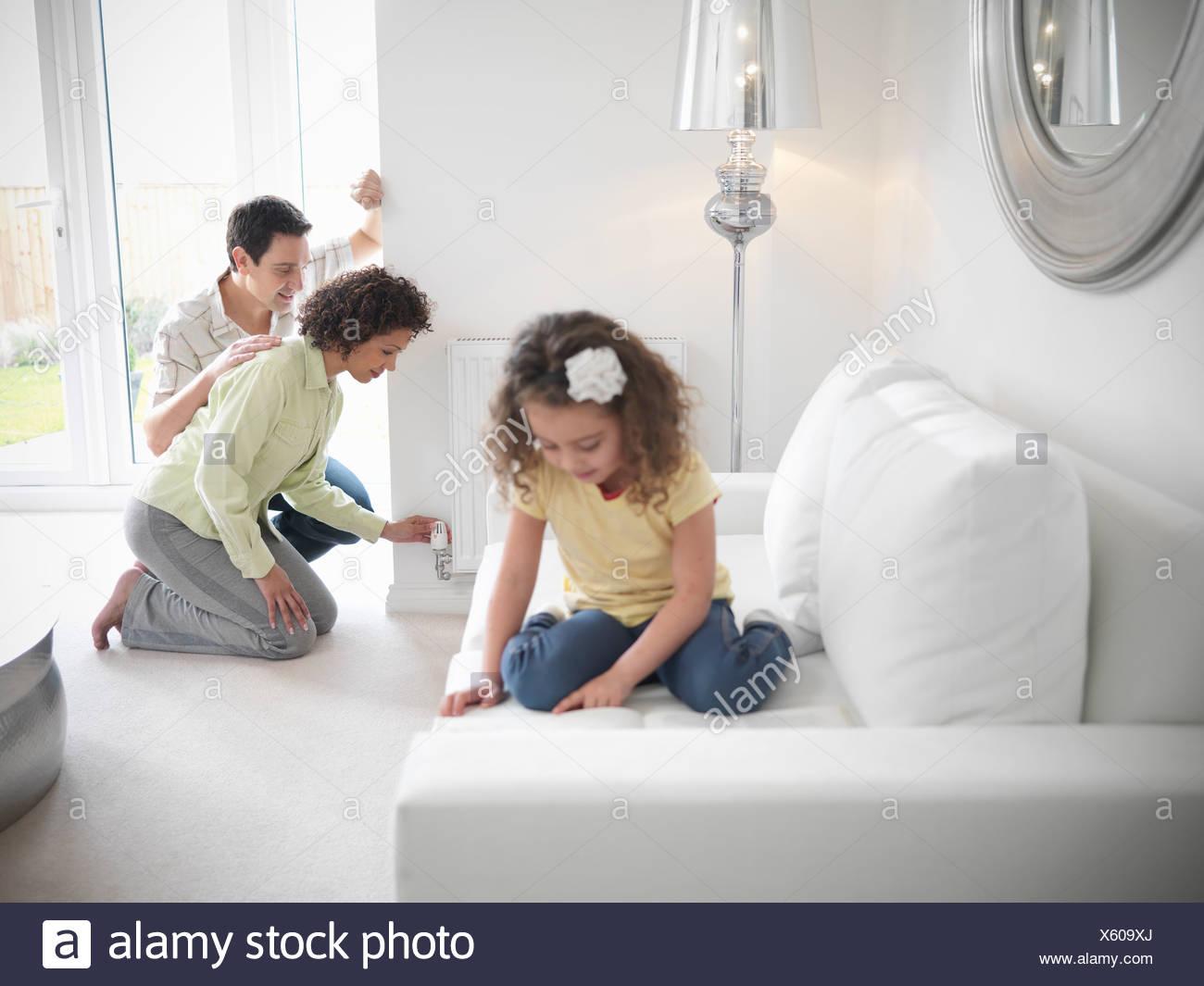 Couple adjusting radiator in living room - Stock Image