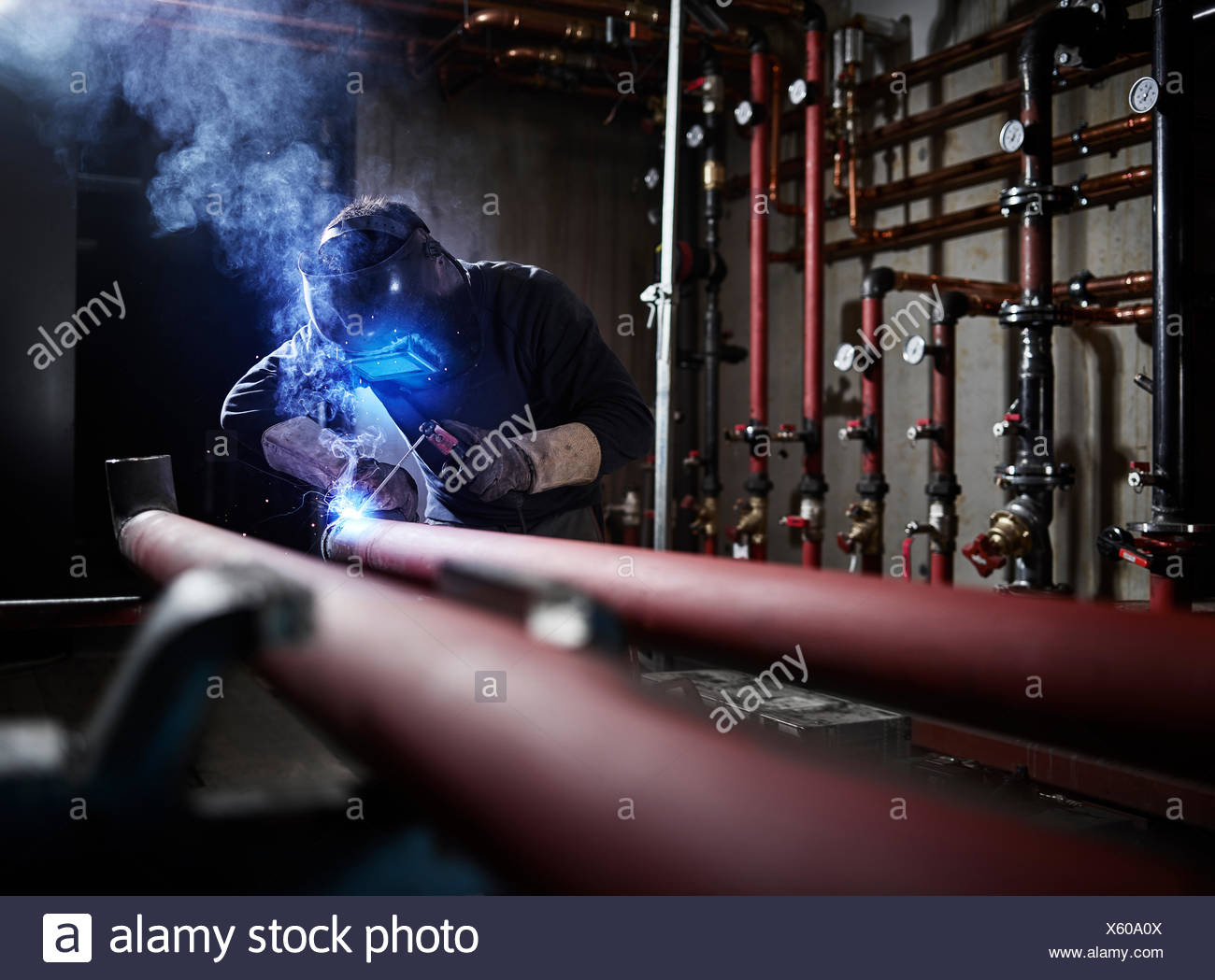 Plant fitter welding mask welding pipes, Austria - Stock Image
