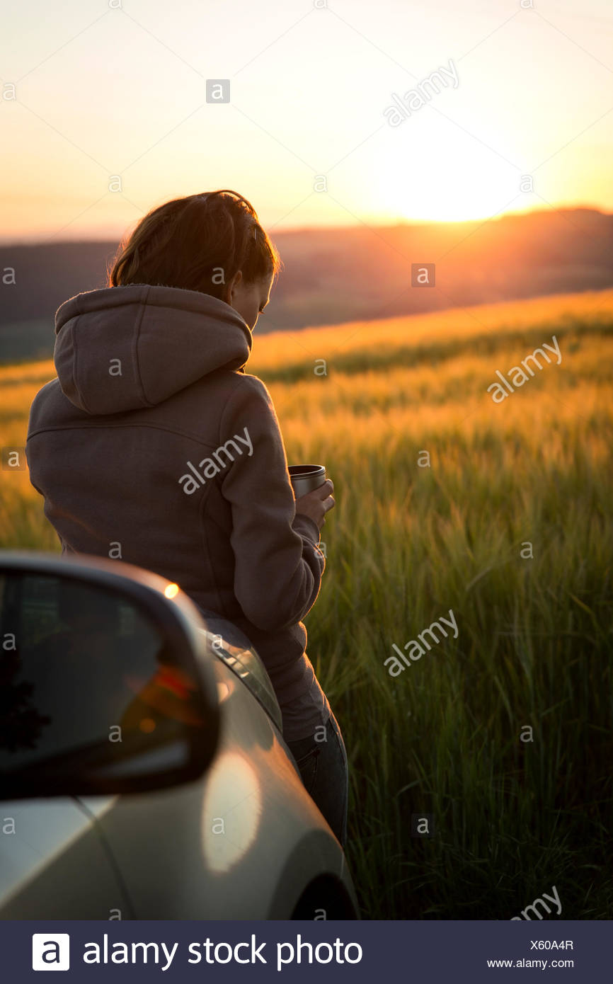Germany, woman leaning on car in front of a field at sunrise - Stock Image