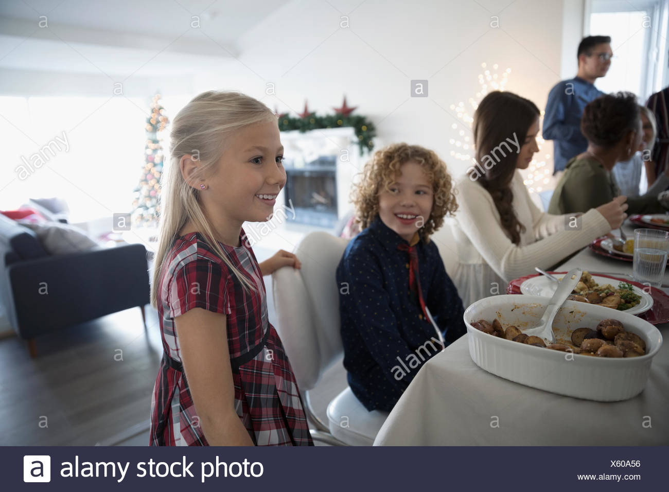 Brother and sister enjoying family Christmas dinner at table - Stock Image