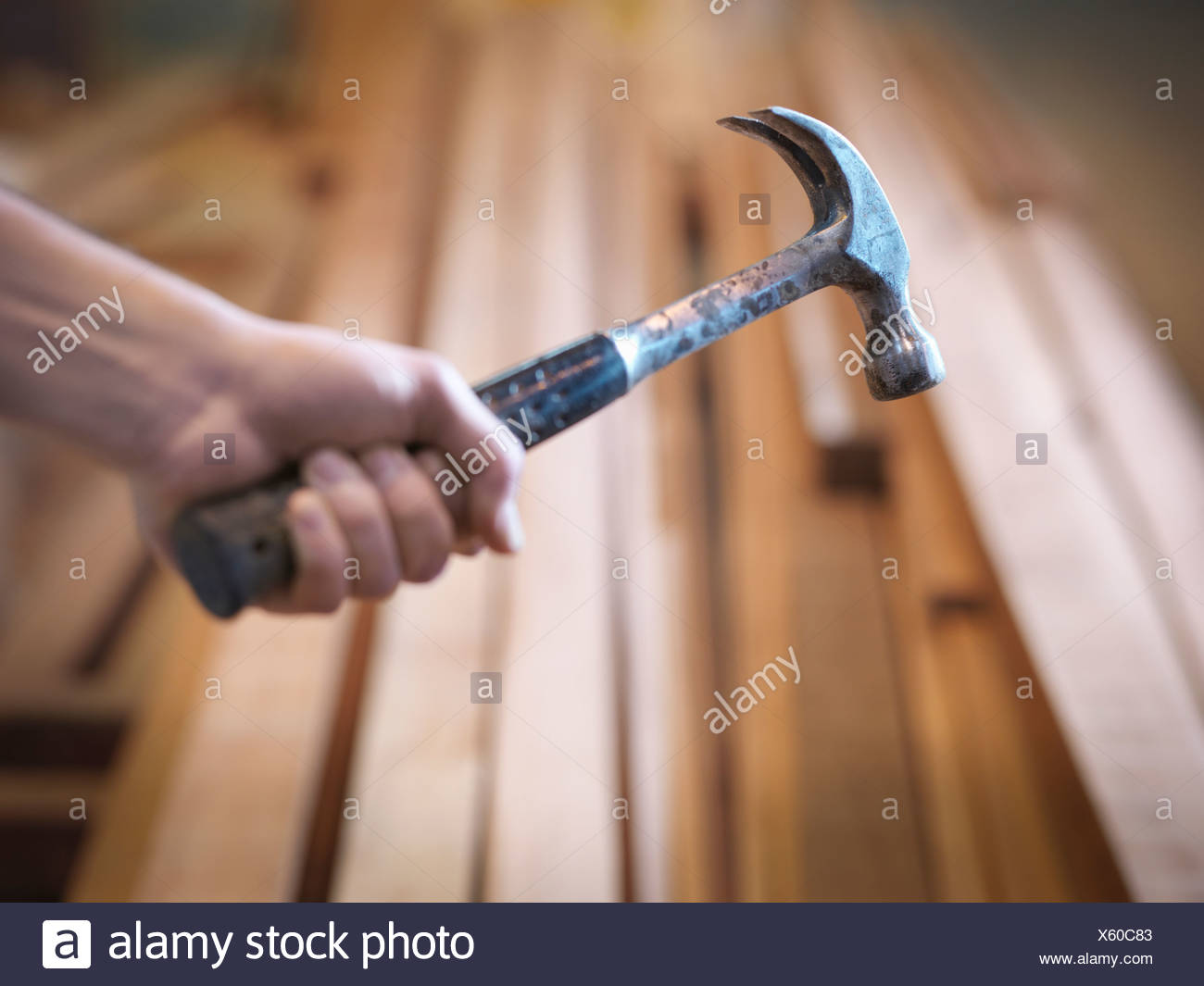 Hand holding hammer next to timber Stock Photo