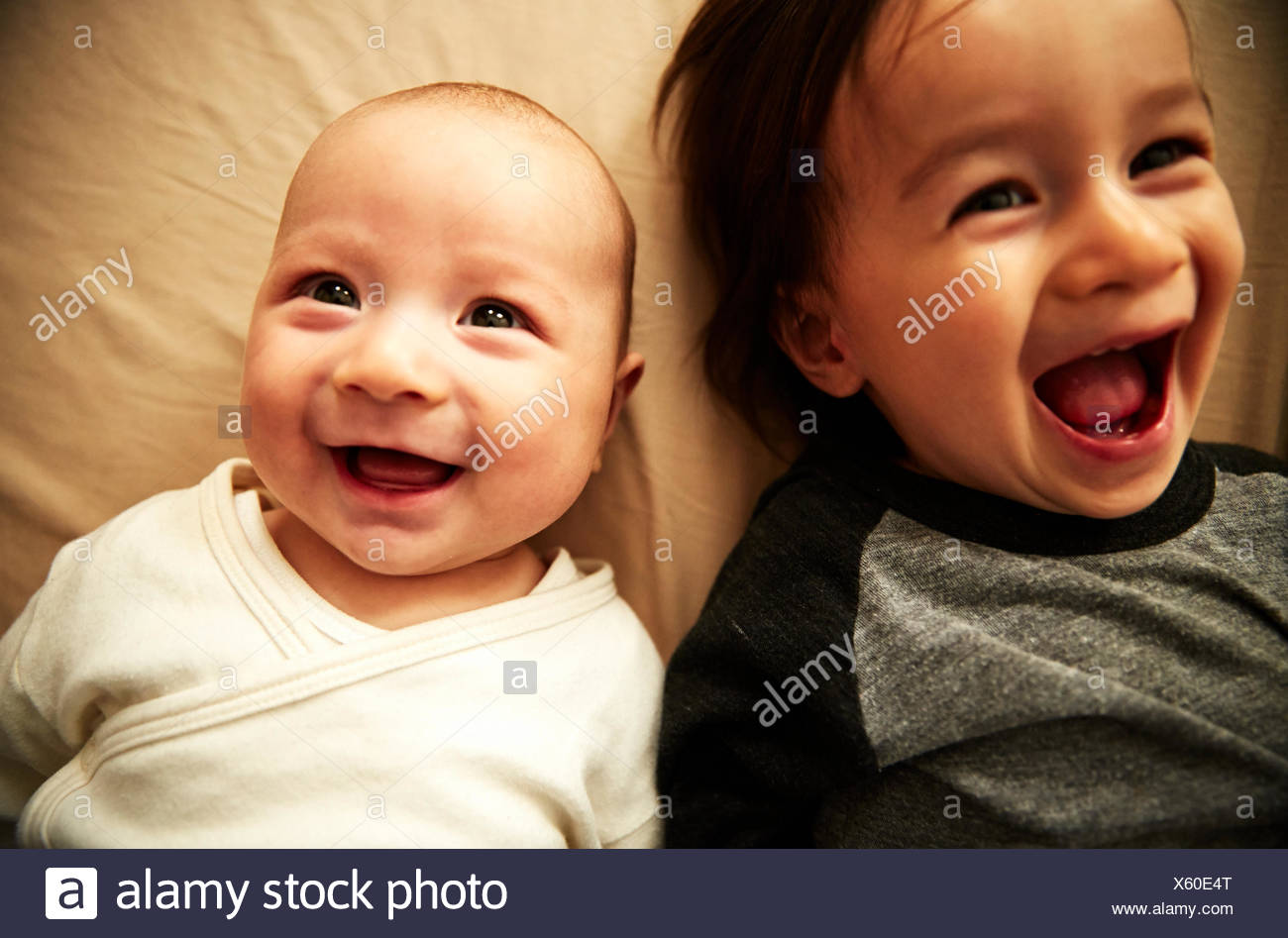 Overhead view of male toddler and baby brother laughing - Stock Image