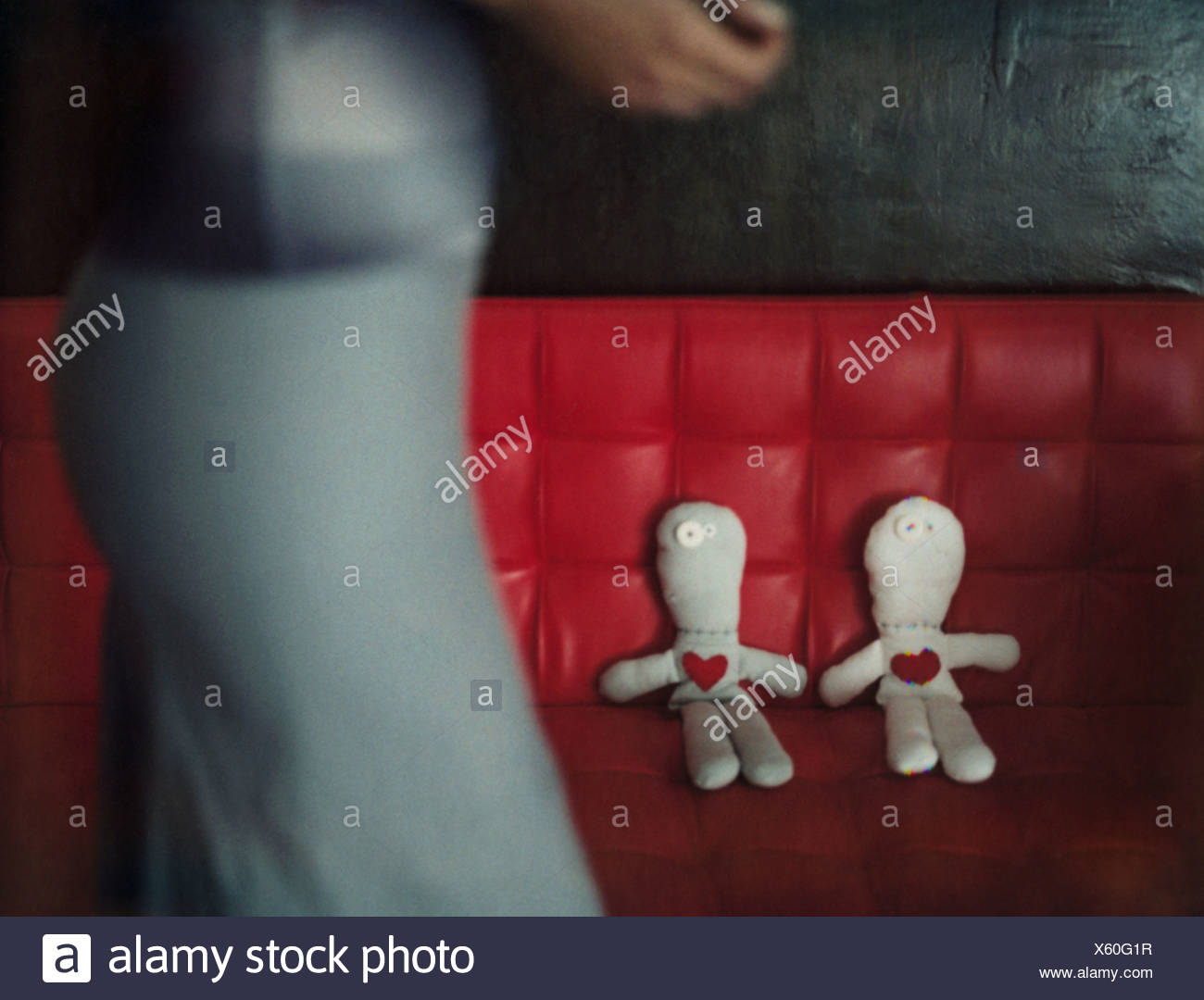 Woman walking by two rag dolls on red sofa, focus on dolls in background - Stock Image