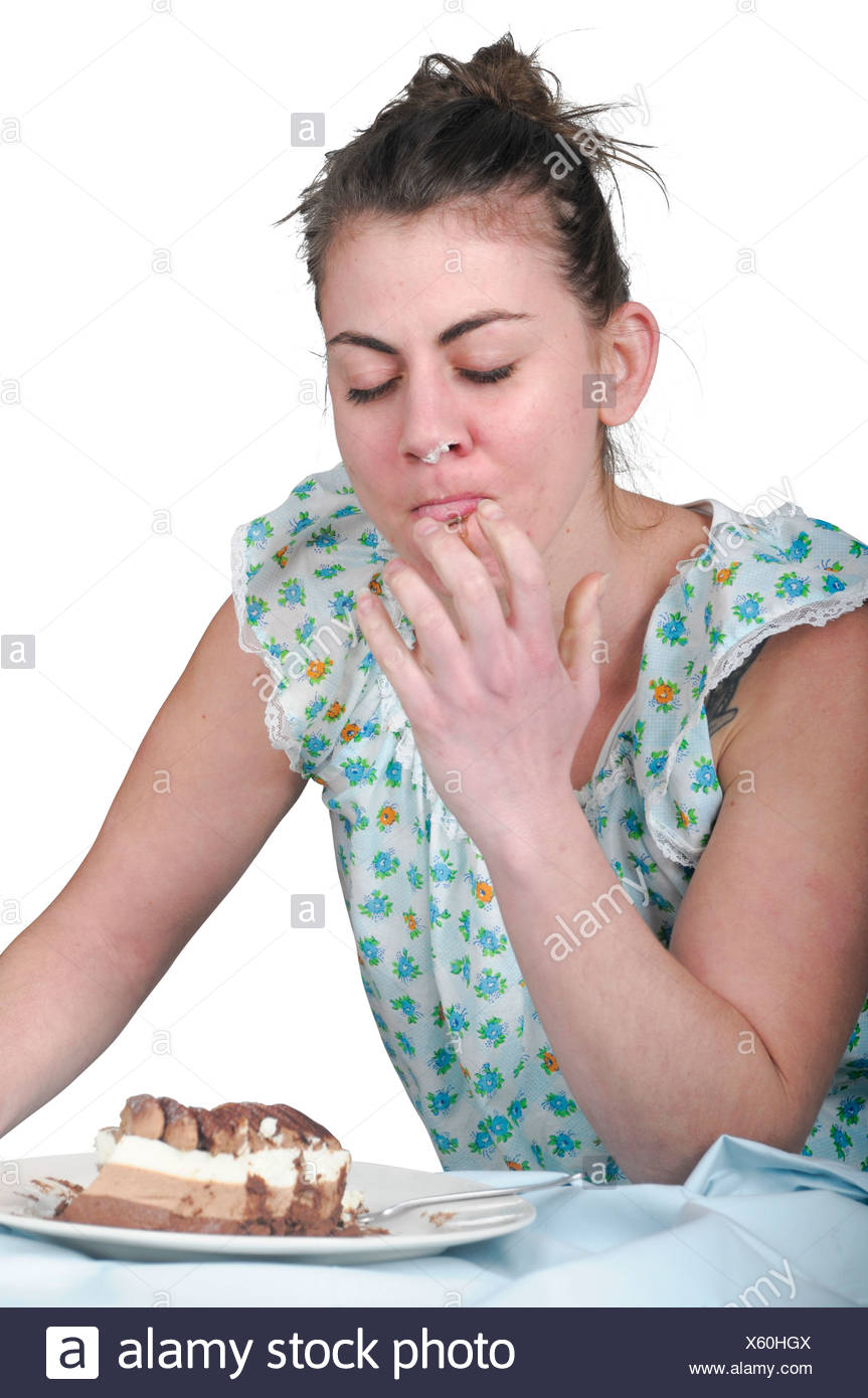 Female eating disorder. Young woman craves a cream cake late at night. - Stock Image