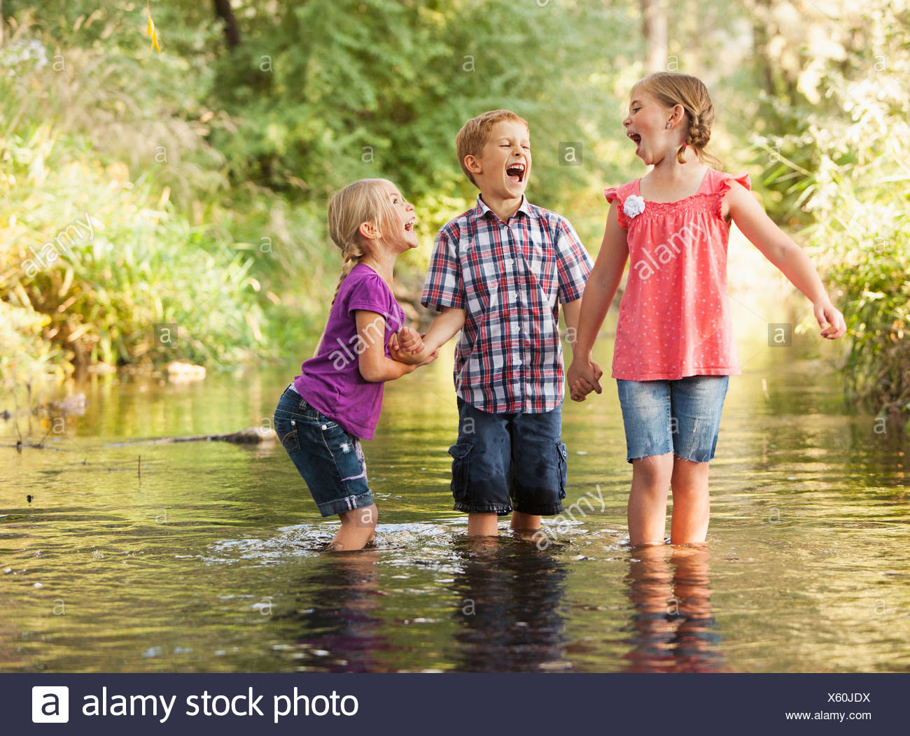 USA, Utah, Lehi, Three kids (4-5, 6-7) playing together in small stream - Stock Image