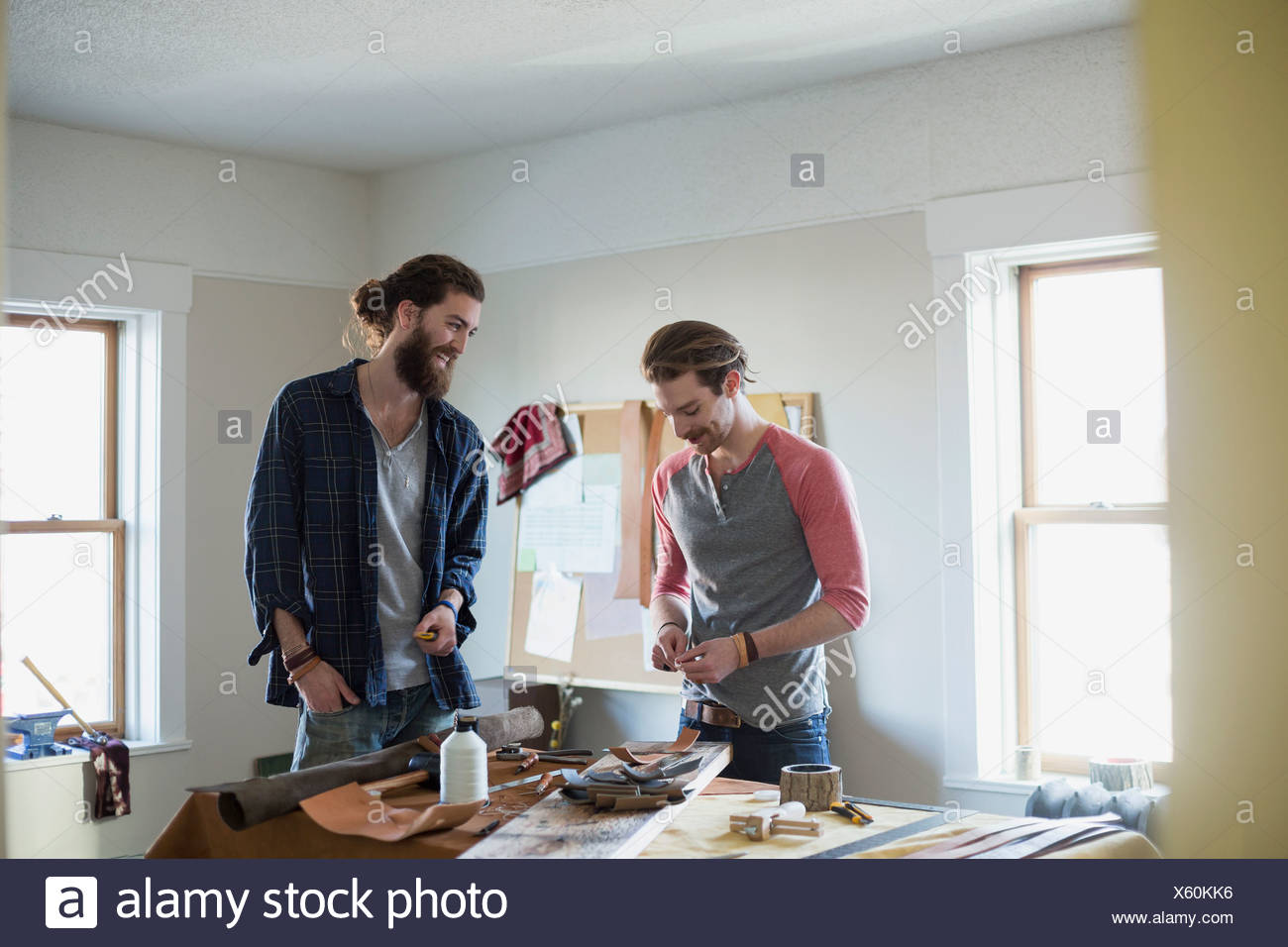 Young men making belts with equipment on table - Stock Image