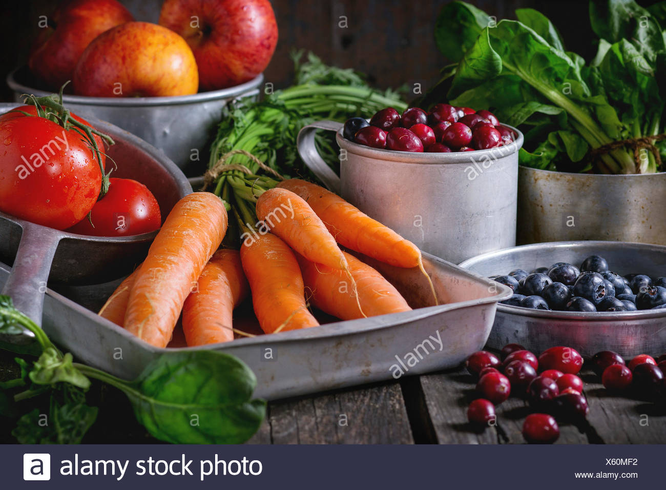 Assortment of fresh fruits, vegetables and berries. Bunch of carrots, spinach, tomatoes and red apples, blueberries and cranberr Stock Photo
