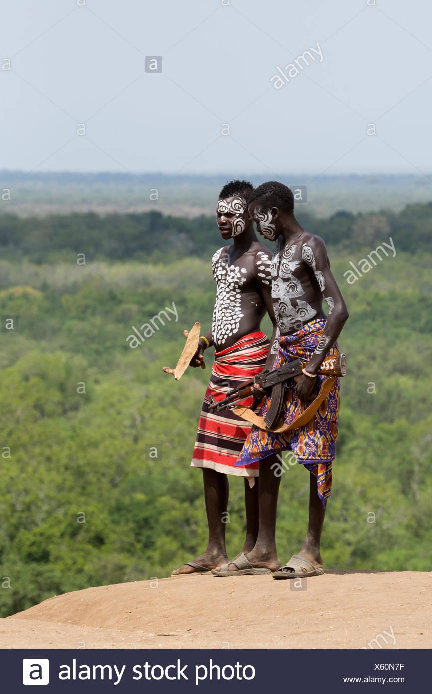 Young male Karo tribe boys with AK-47 rifle . Omo Valley, Ethiopia - Stock Image