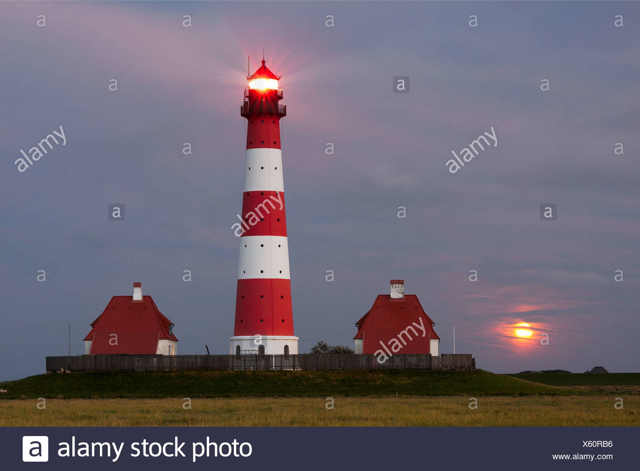 Westerhever lighthouse with the full moon rising above the horizon, Westerheversand, North Friesland district - Stock Image