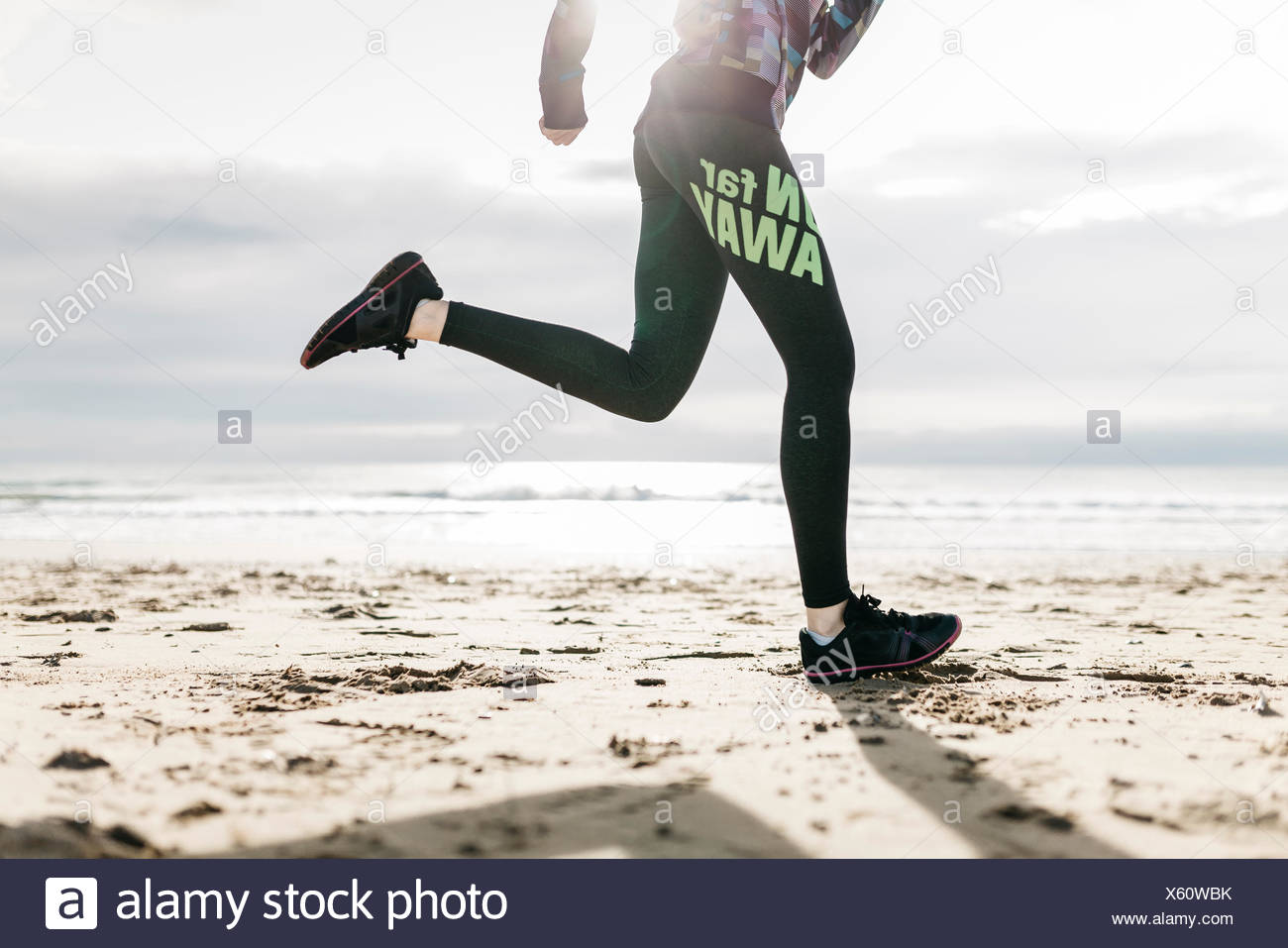 Spain, Tarragona, Legs and sneakers running in the sand of a beach - Stock Image