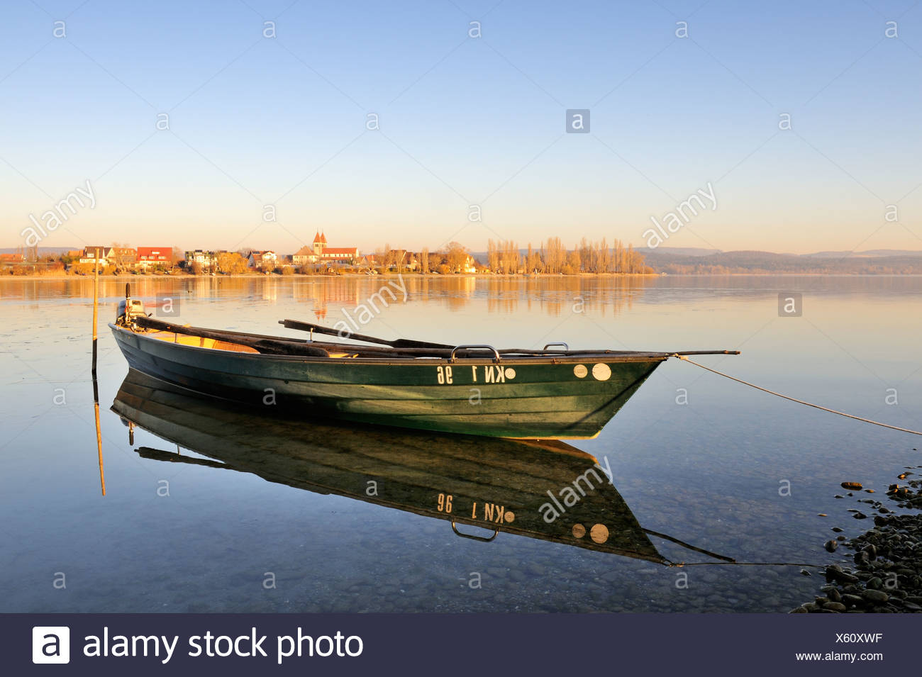 Evening mood with a fishing boat on the shore of the island of Reichenau, at the rear, the Church of St. Peter and Paul on the - Stock Image