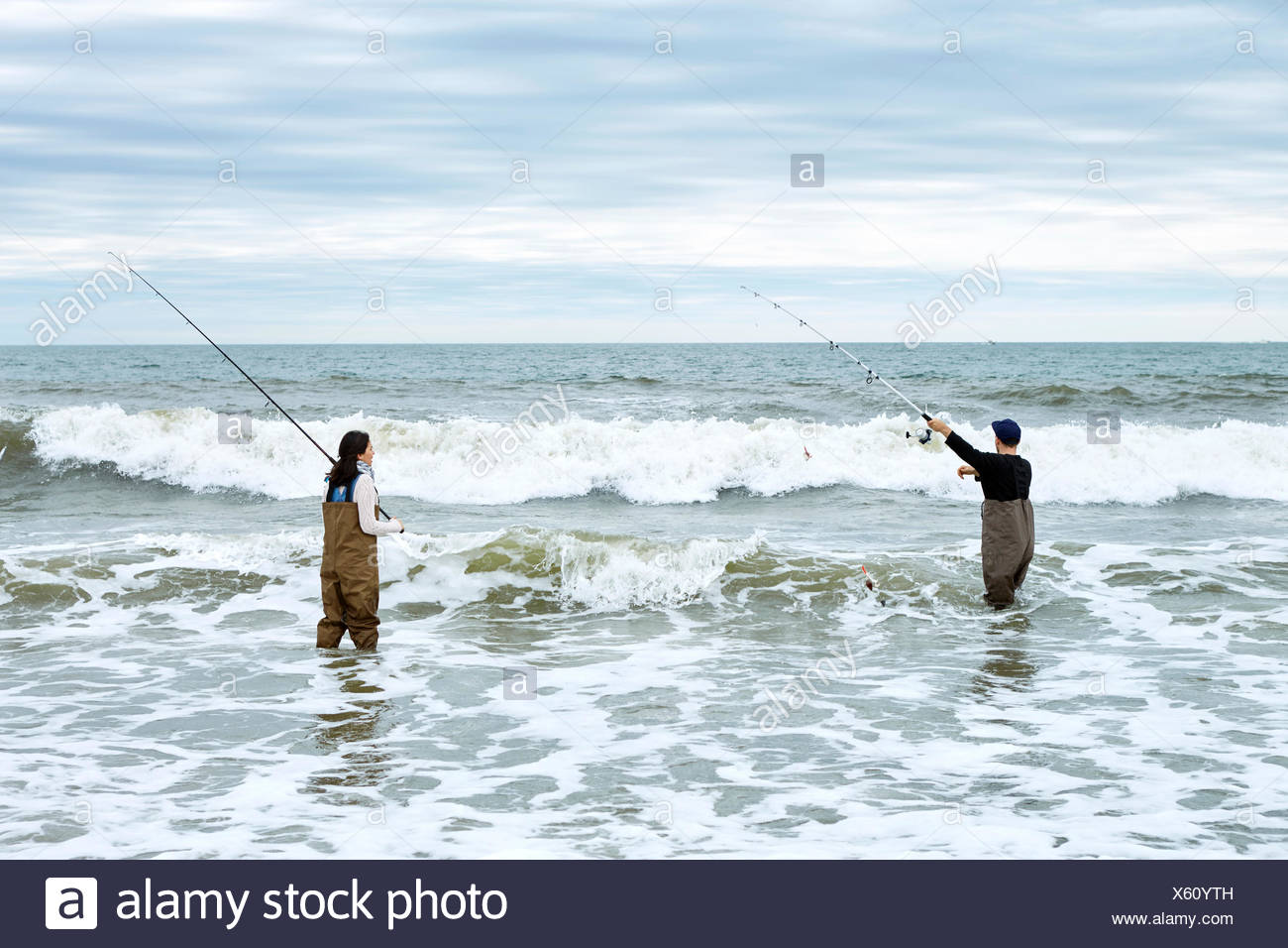 Young couple in waders, casting off sea fishing rods in sea Stock Photo