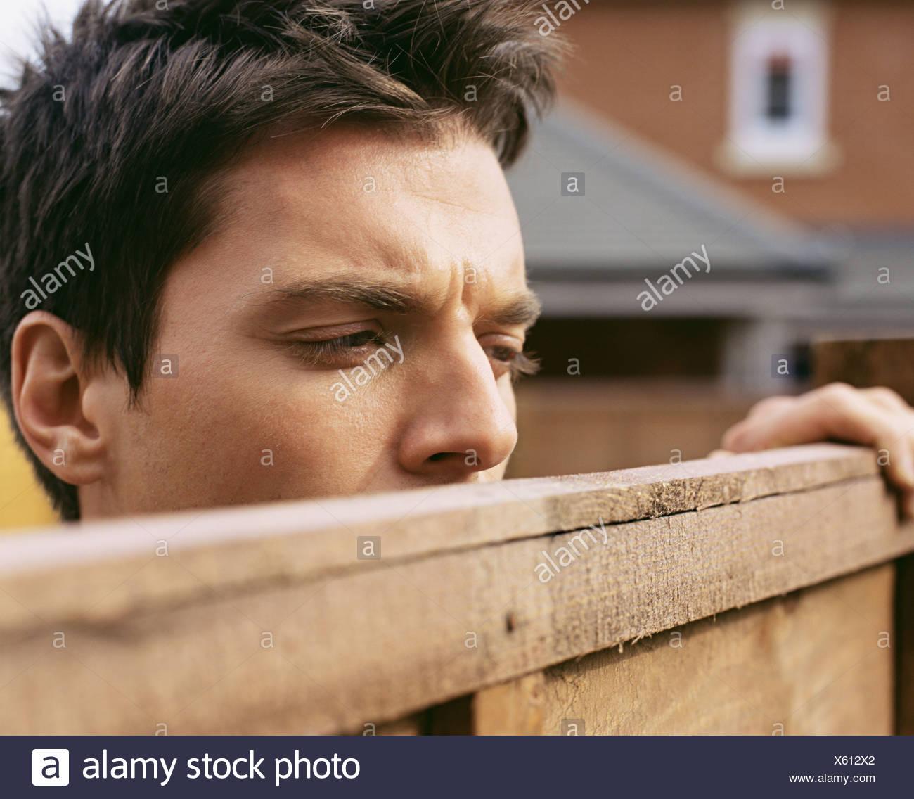 Man looking over garden fence Stock Photo