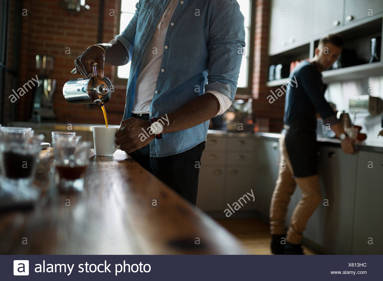 Entrepreneurial coffee roasters pouring coffee in kitchen - Stock Image