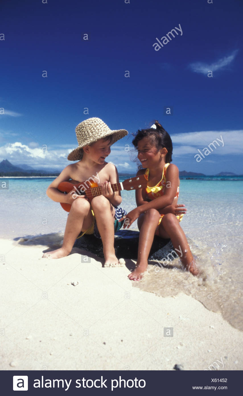 Boy in beach hat with ukulele serenades his friend - Stock Image