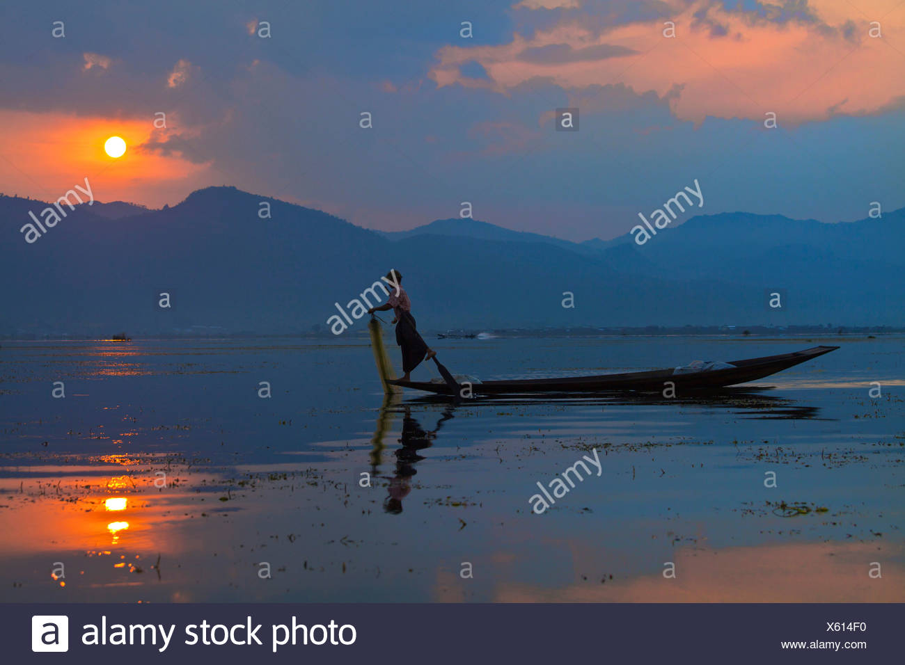 FISHING at dawn is still done in the traditonal way with small wooden boats, fishing nets and leg rowing - INLE LAKE, Burma - Stock Image