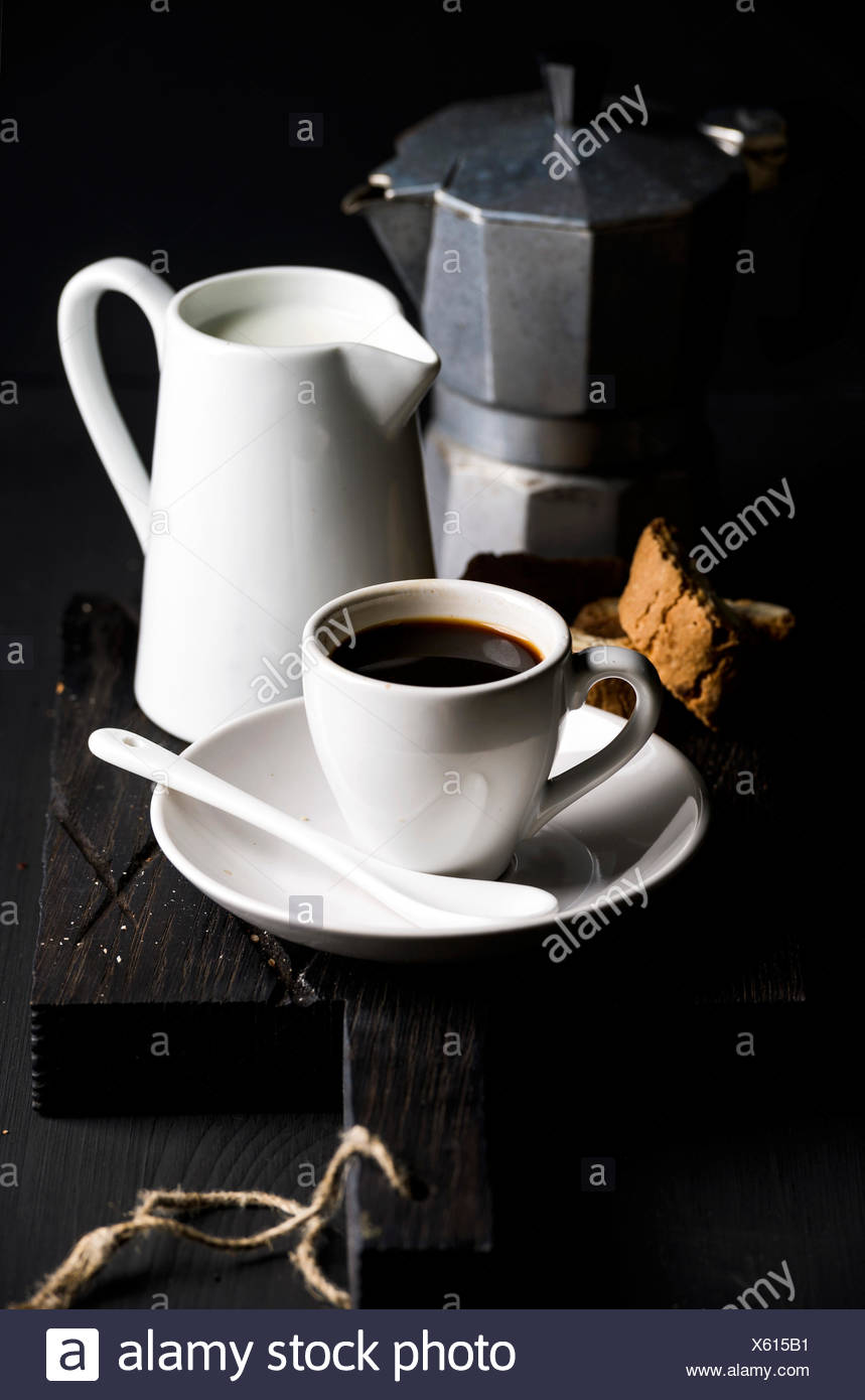 Italian coffee set. Cup of hot espresso, creamer with milk, cantucci and moka pot on a rustic wooden board, dark background, sel - Stock Image