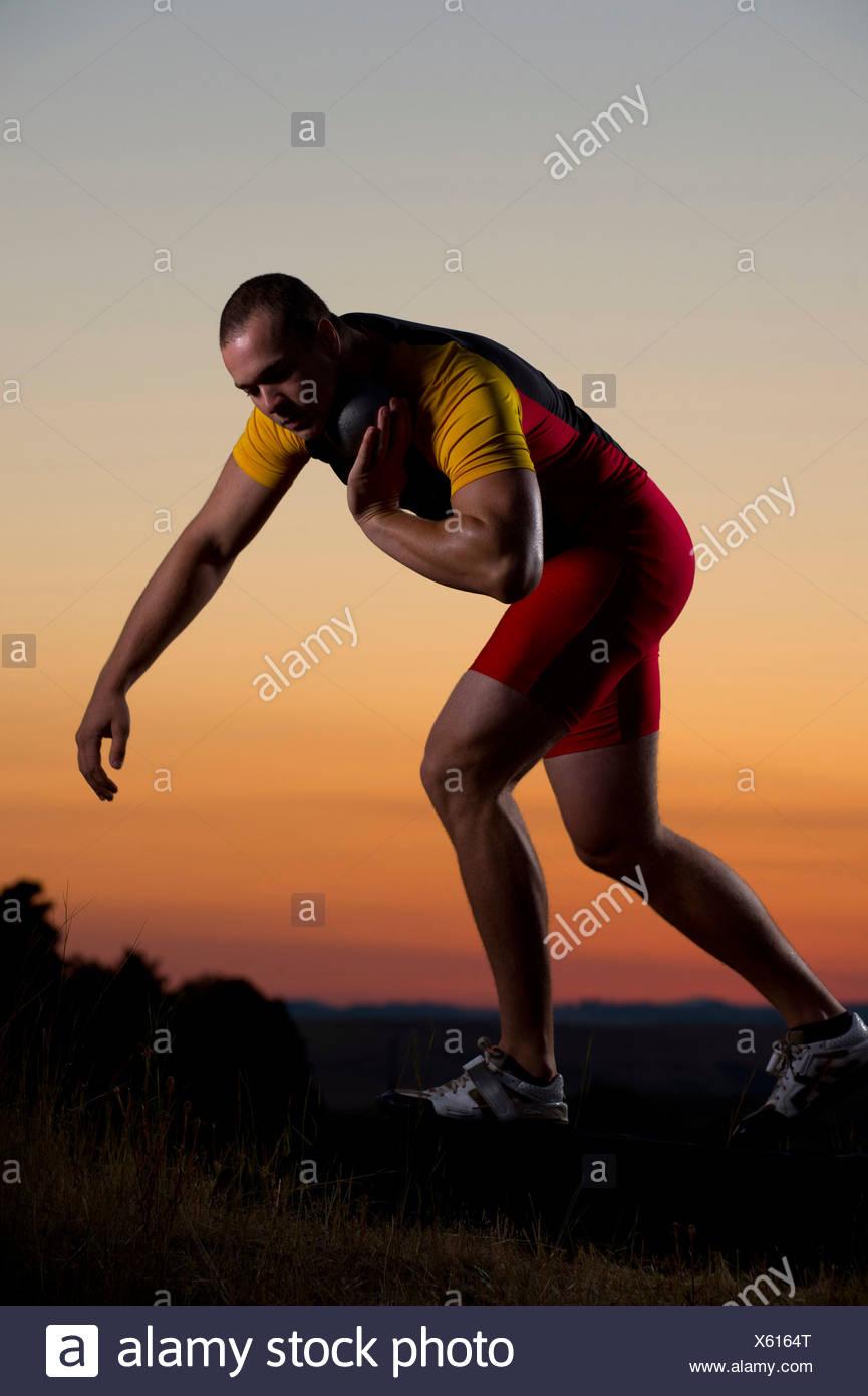Young man preparing to throw shot put at sunset - Stock Image