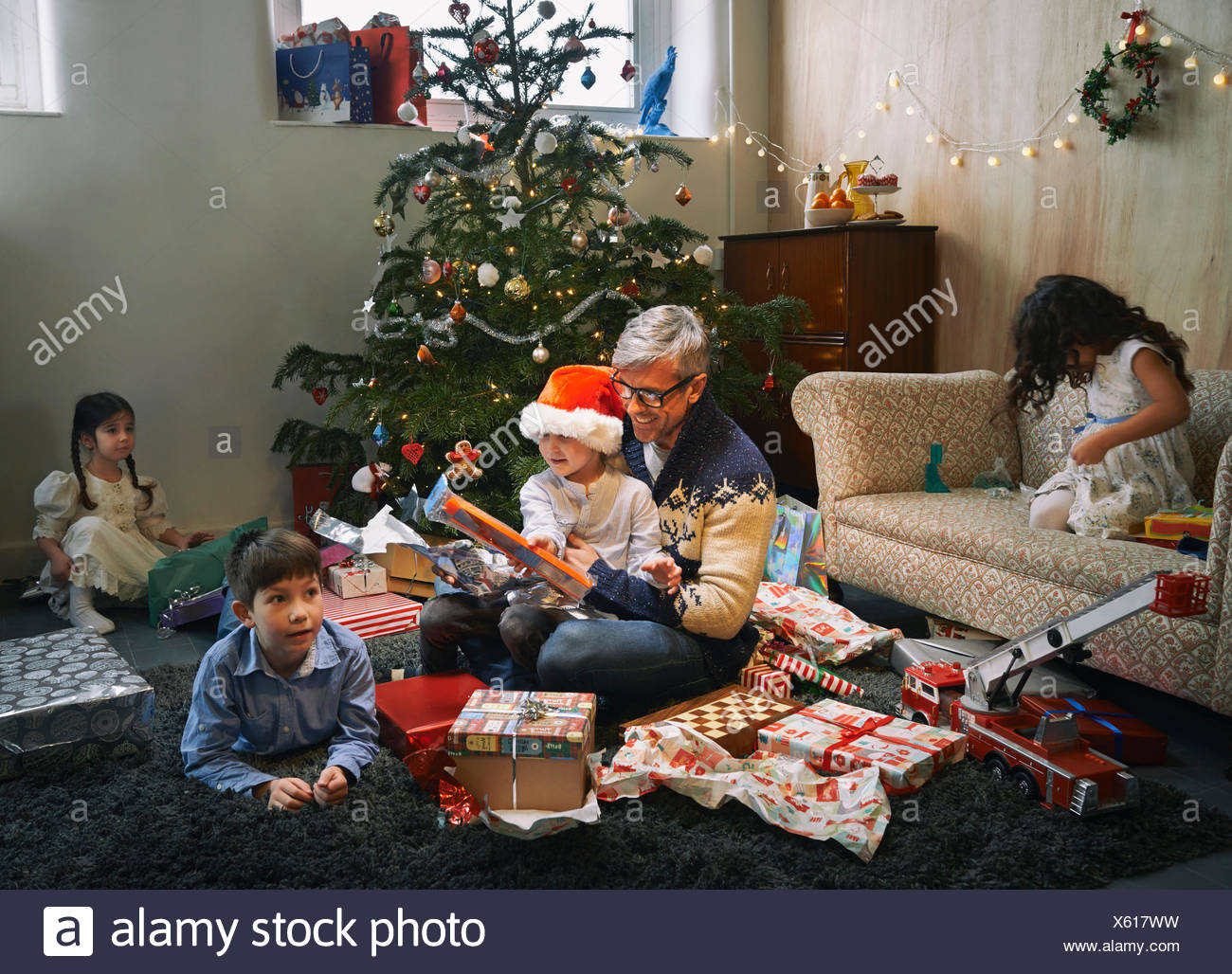 Father and four children opening christmas gifts in sitting room - Stock Image