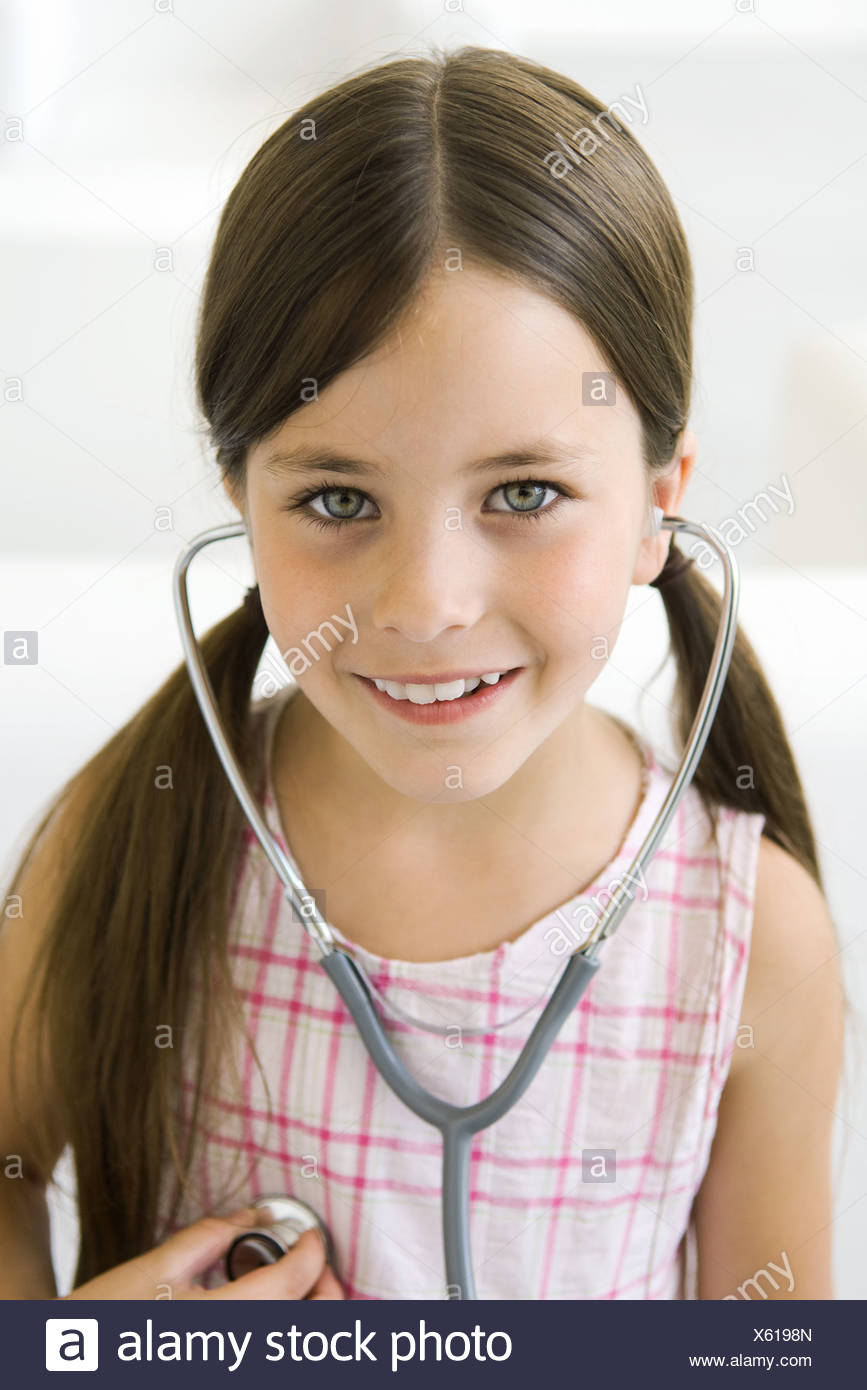Girl listening to her own heart through stethoscope - Stock Image