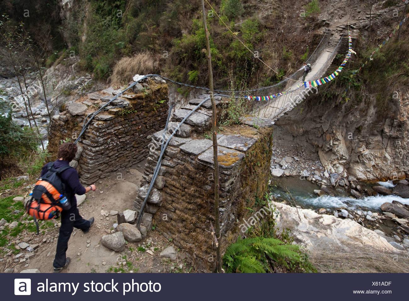 A male trekker approaches a footbridge while a female trekker pauses on the bridge ahead. - Stock Image