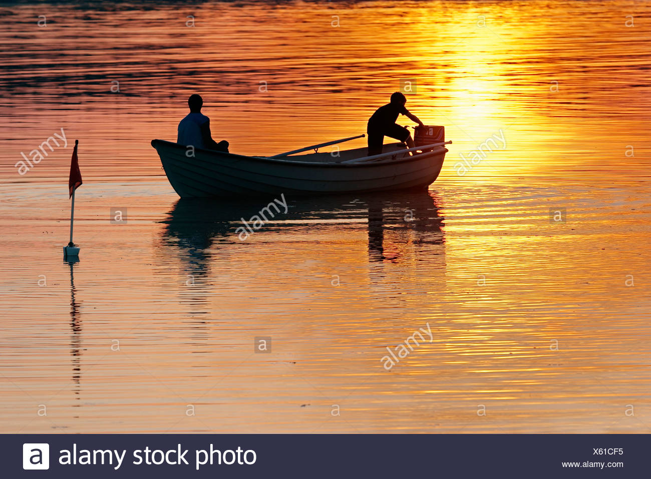 Side view of two men in motorboat with engine failure in the lake at sunset - Stock Image