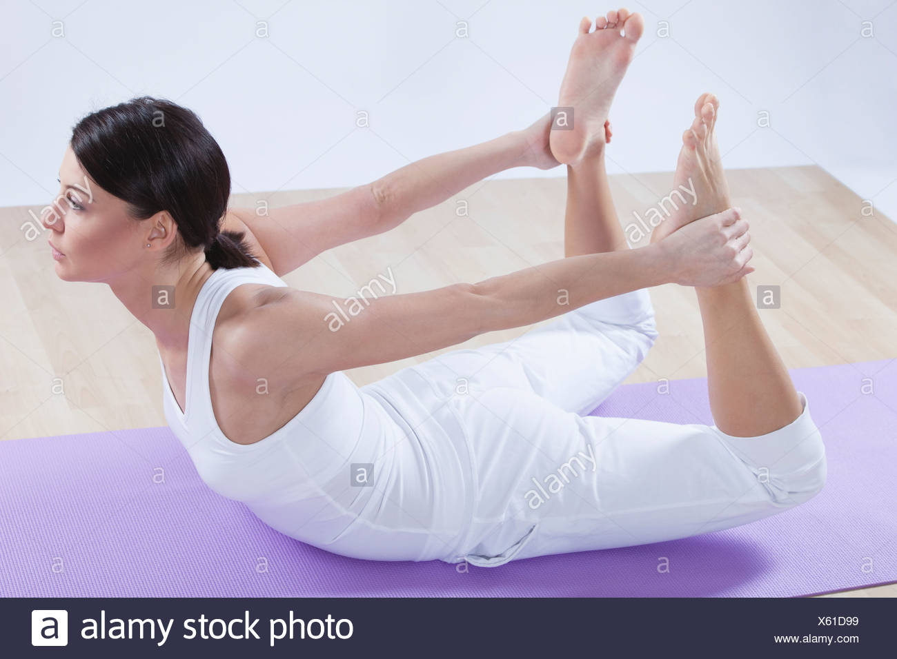 Mid adult woman doing bow pose against white background - Stock Image