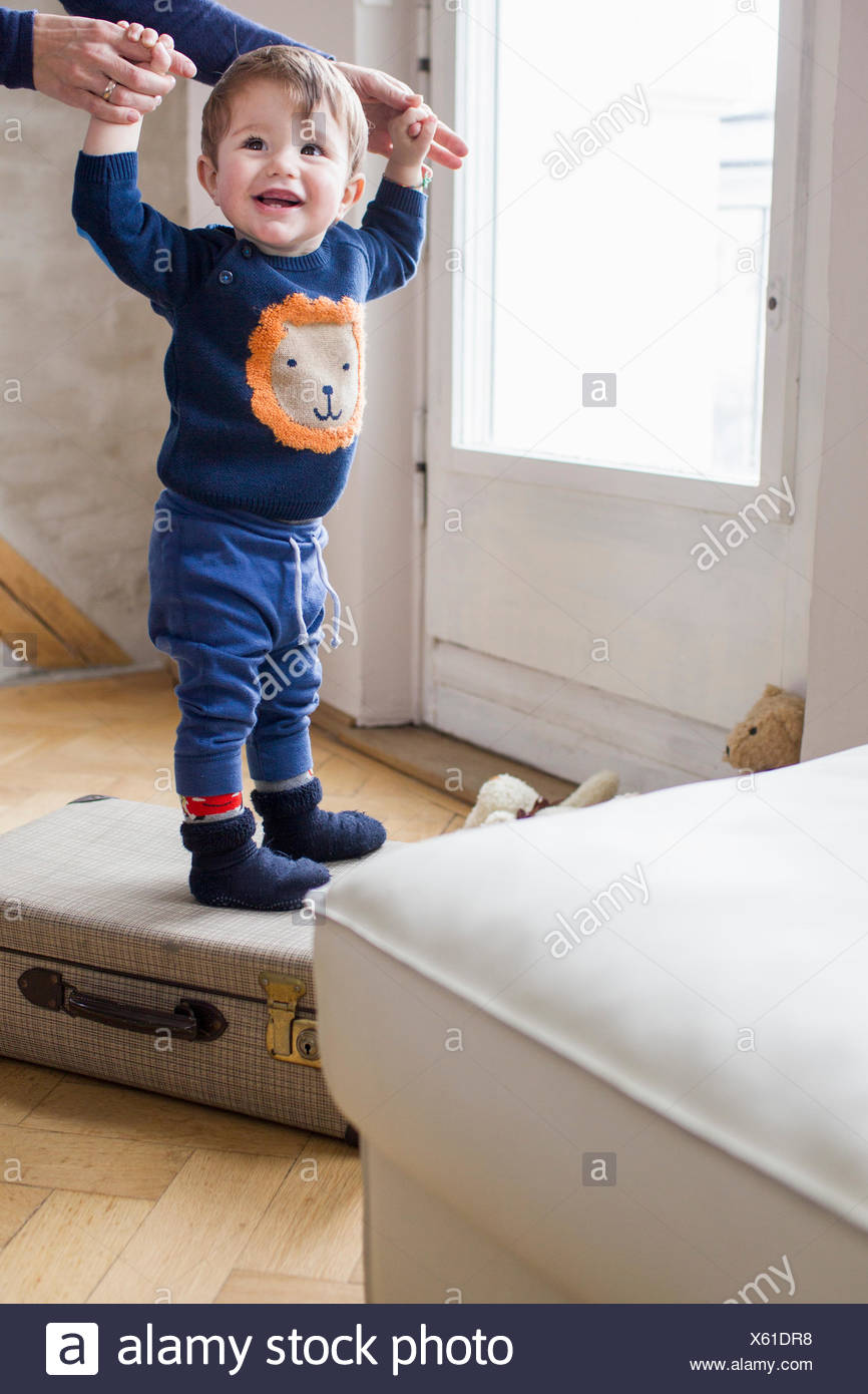 Baby boy holding mothers hands and standing on suitcase - Stock Image