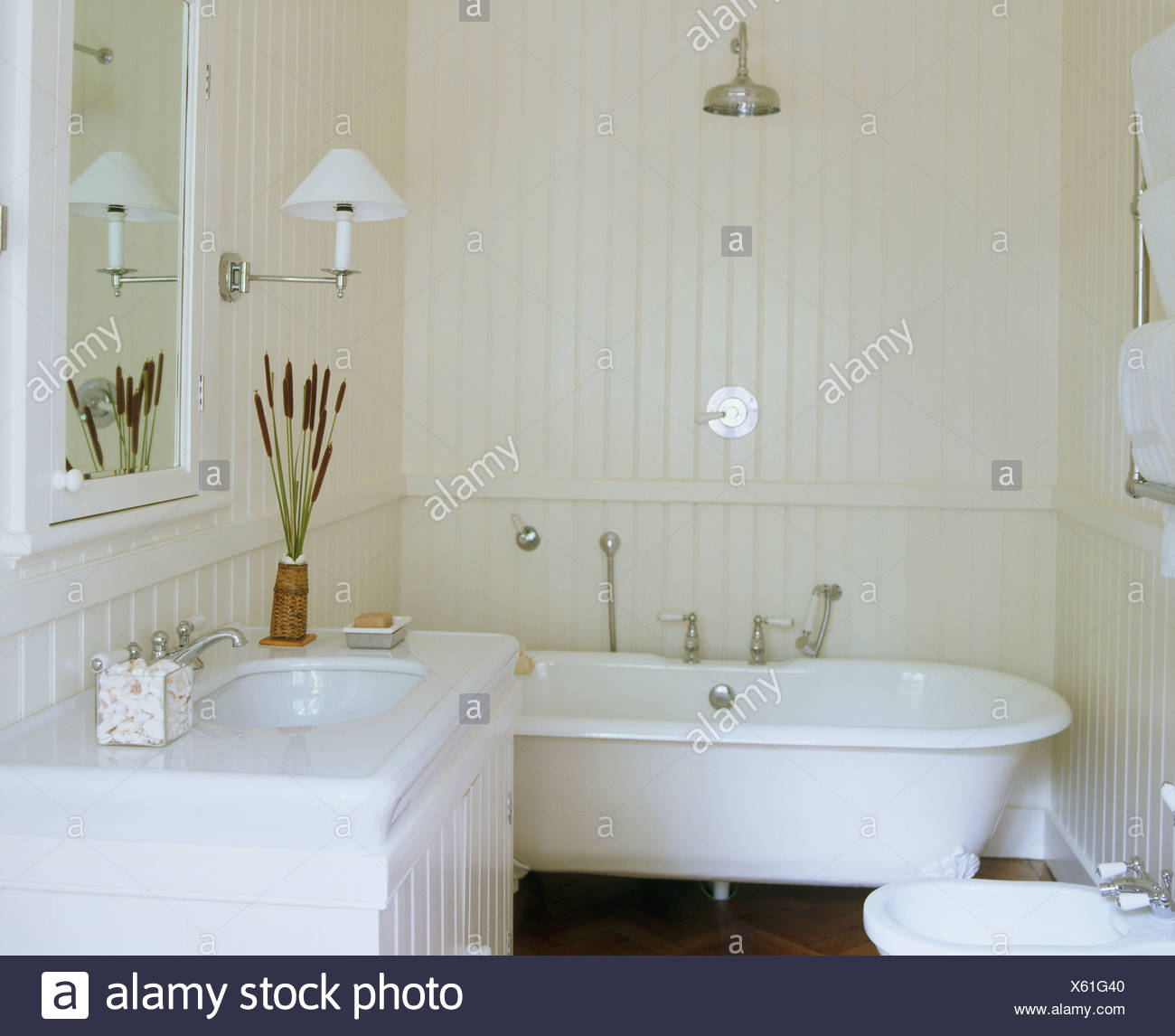 Chrome shower above roll-top bath in white bathroom with white ...