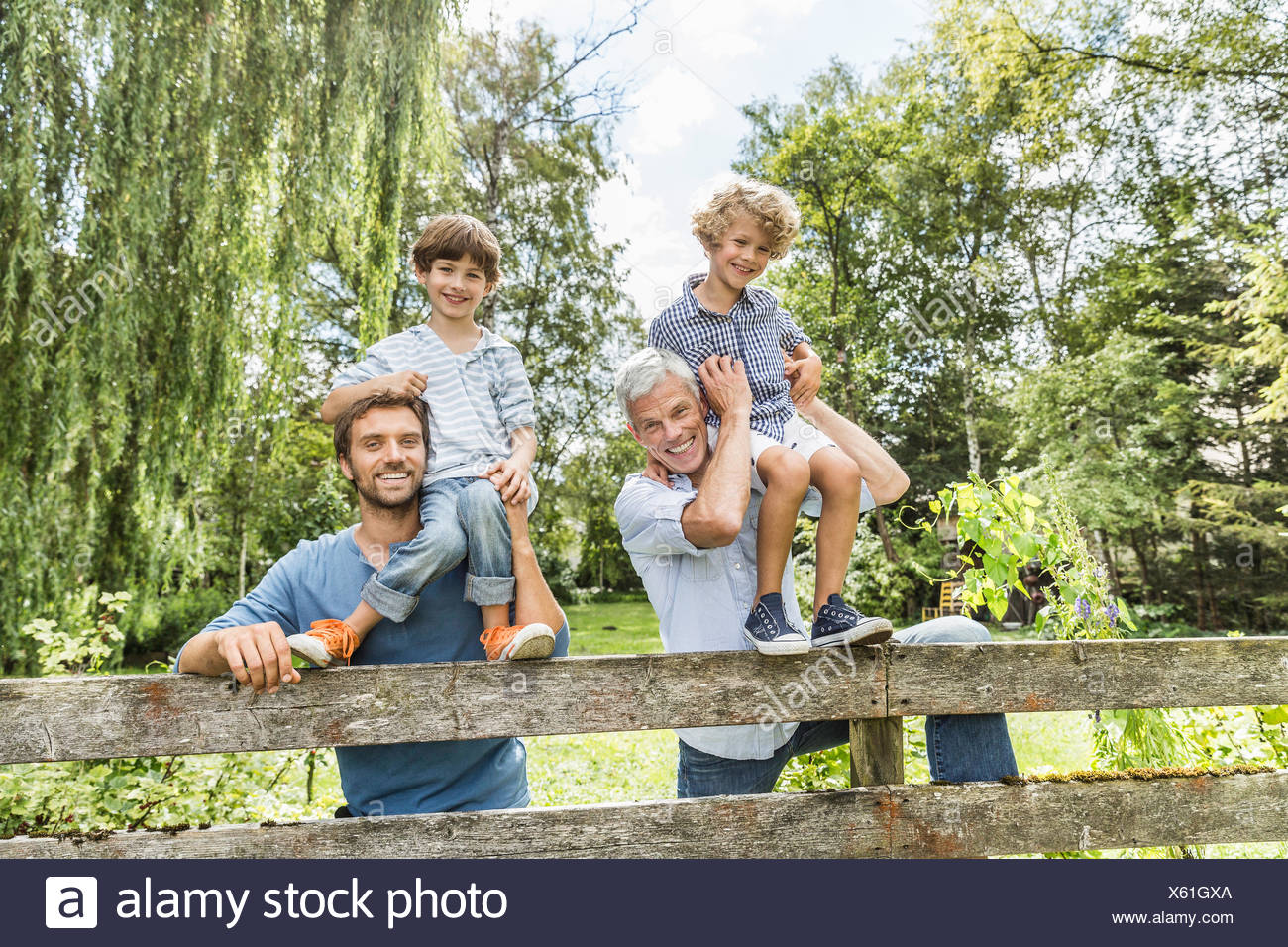 Portrait of three generation family males in garden - Stock Image