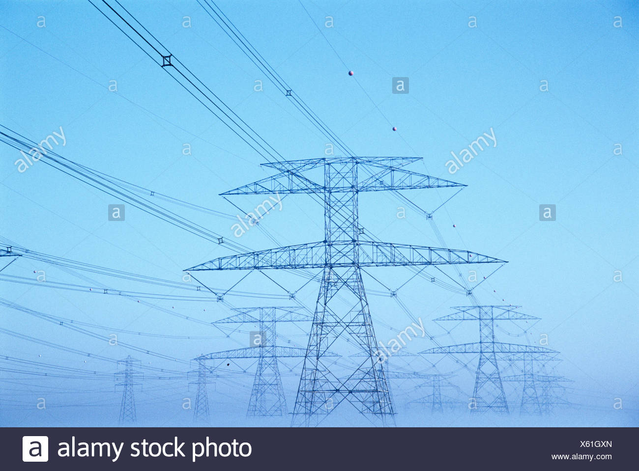 Electricity pylons supporting power lines. - Stock Image