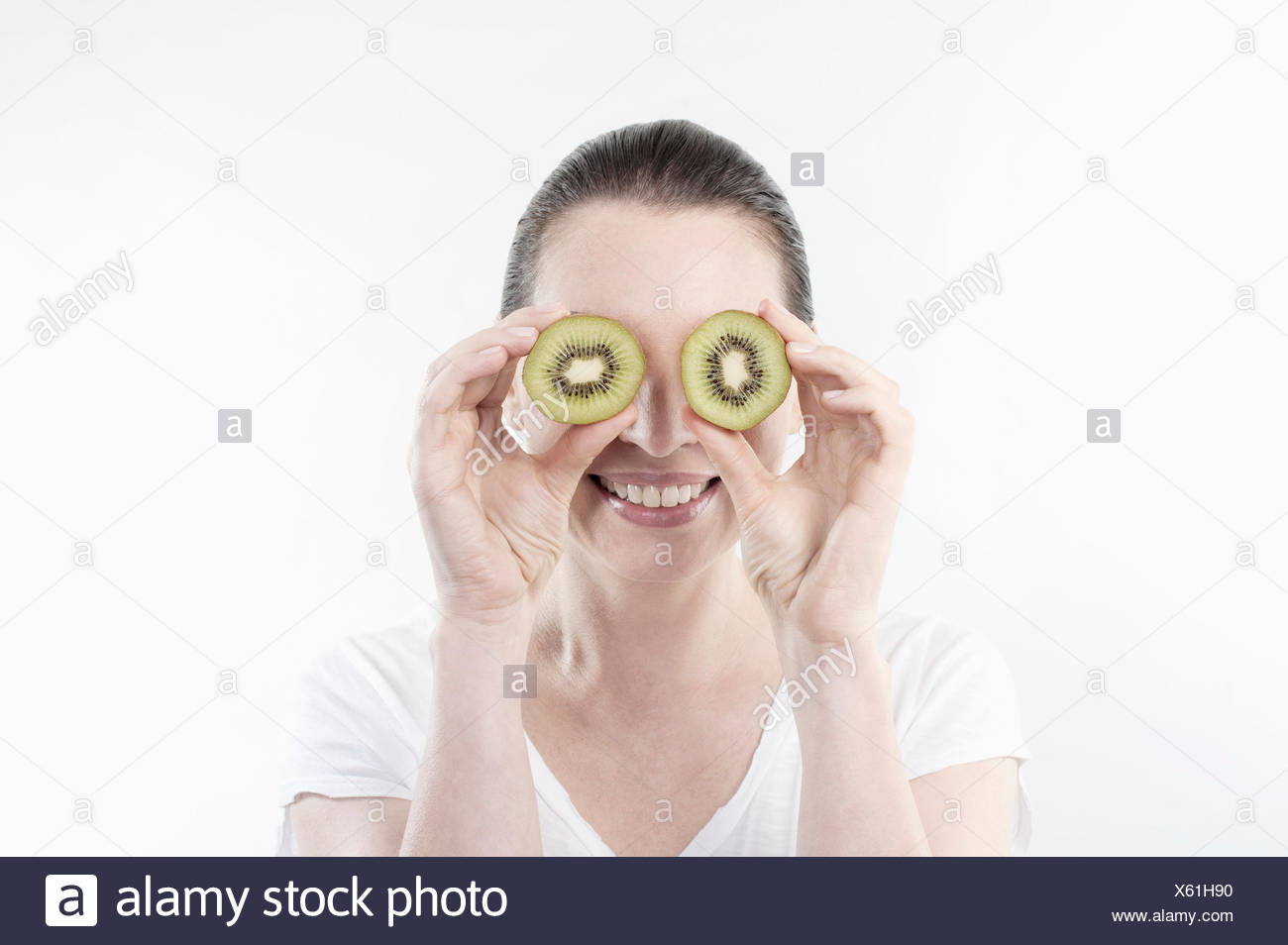 Mature woman holding kiwi slices in front of her eyes, Bavaria, Germany Stock Photo