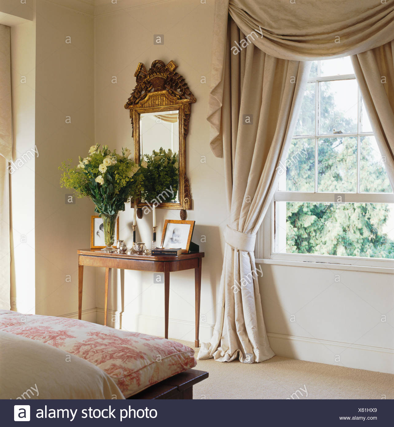 Beige Silk Swagged+tailed Pelmet And Curtains On Window In Country Bedroom  With Antique Gilt Mirror Above Small Table
