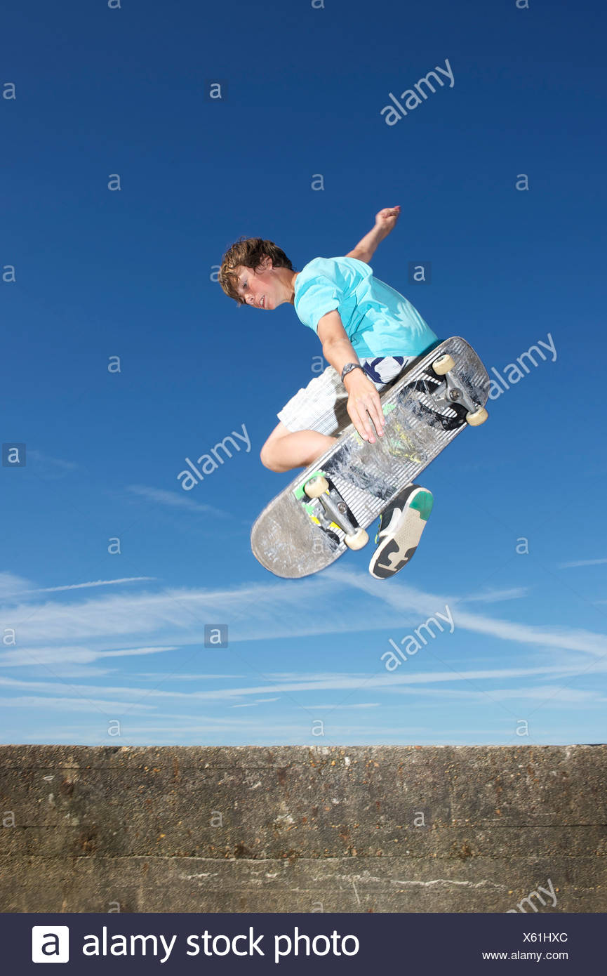 Teenage boy mid air on skateboard - Stock Image