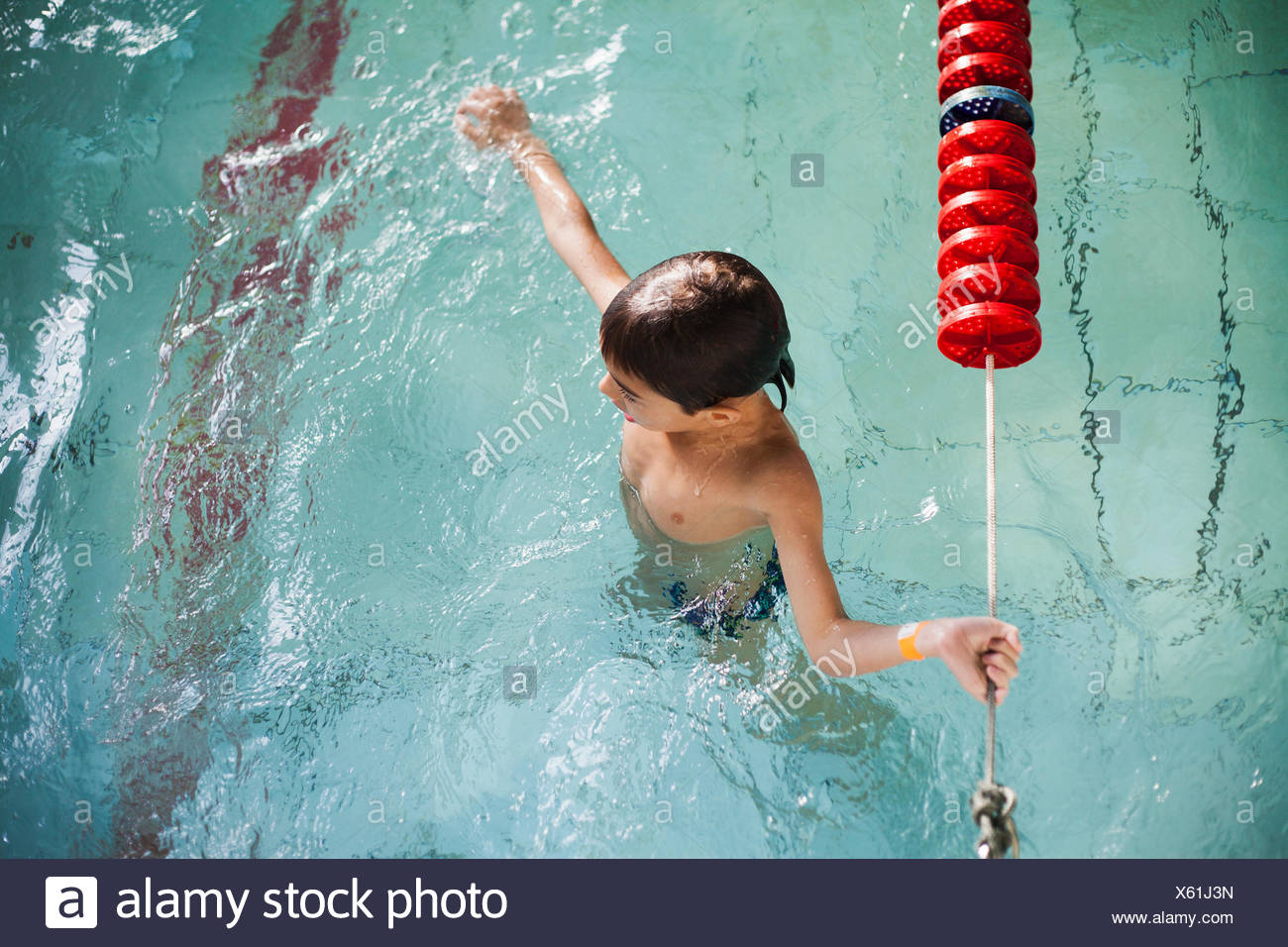 High angle view of boy holding onto rope in swimming pool - Stock Image