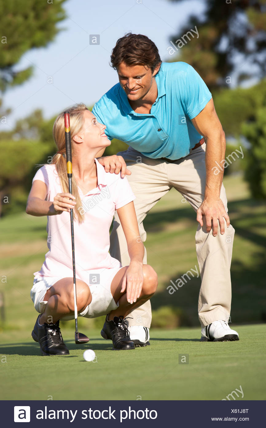 Couple Golfing Golf Course Lining Up Putt On Green - Stock Image