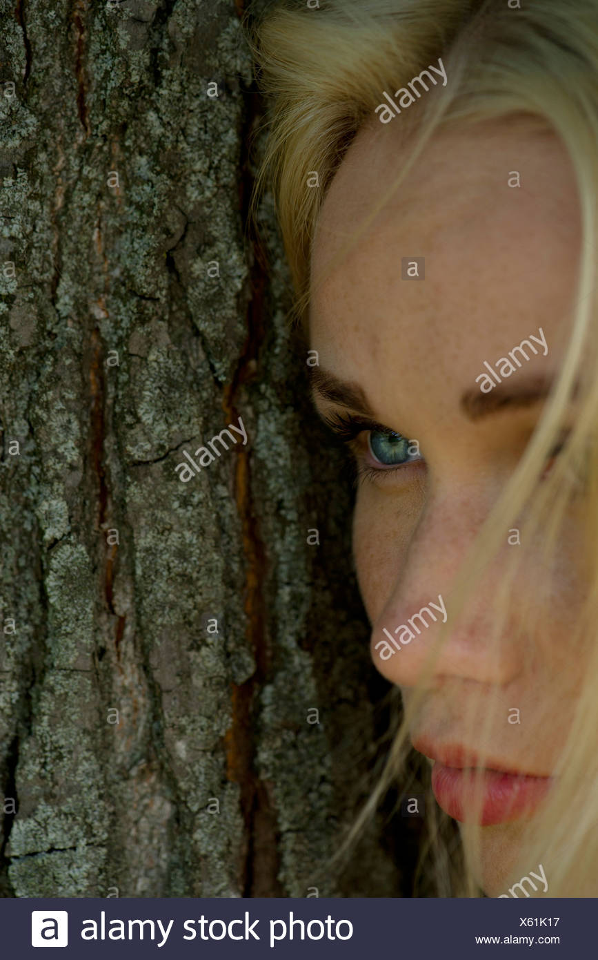 Young woman leaning against tree trunk, looking away sadly - Stock Image