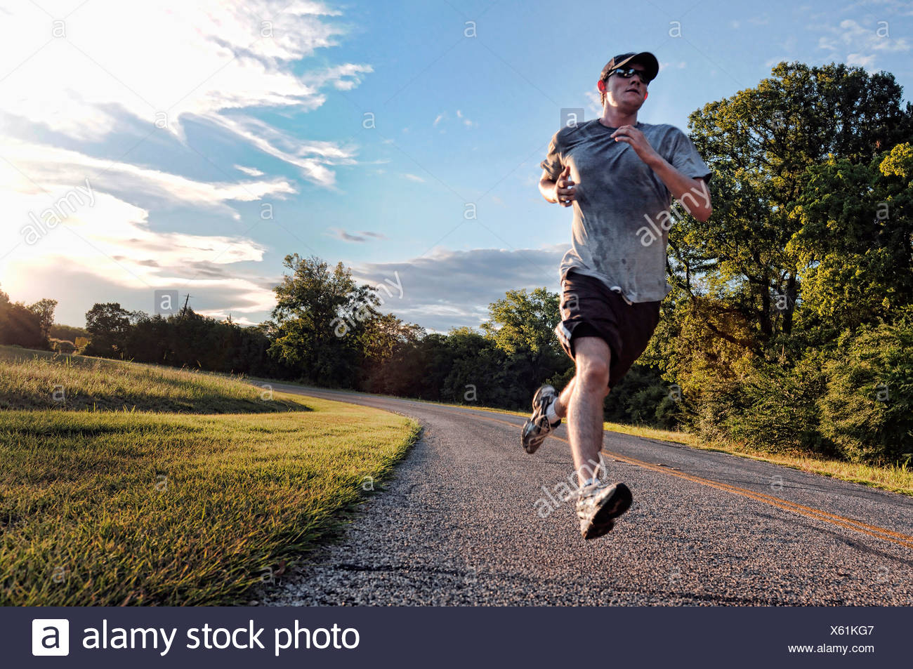 A young man runs along a road during a colorful sunset. - Stock Image